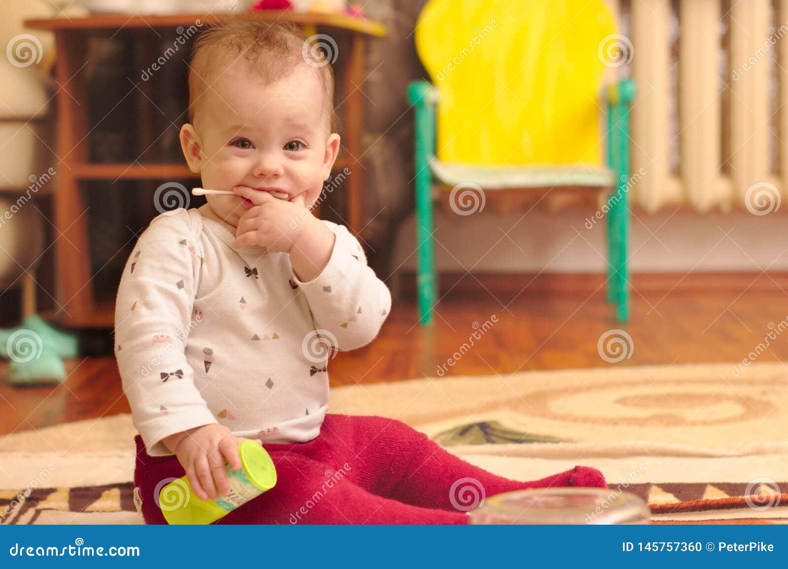 Mały dziecko siedzi na podłodze w pokoju i bawić się z uszatymi kijami