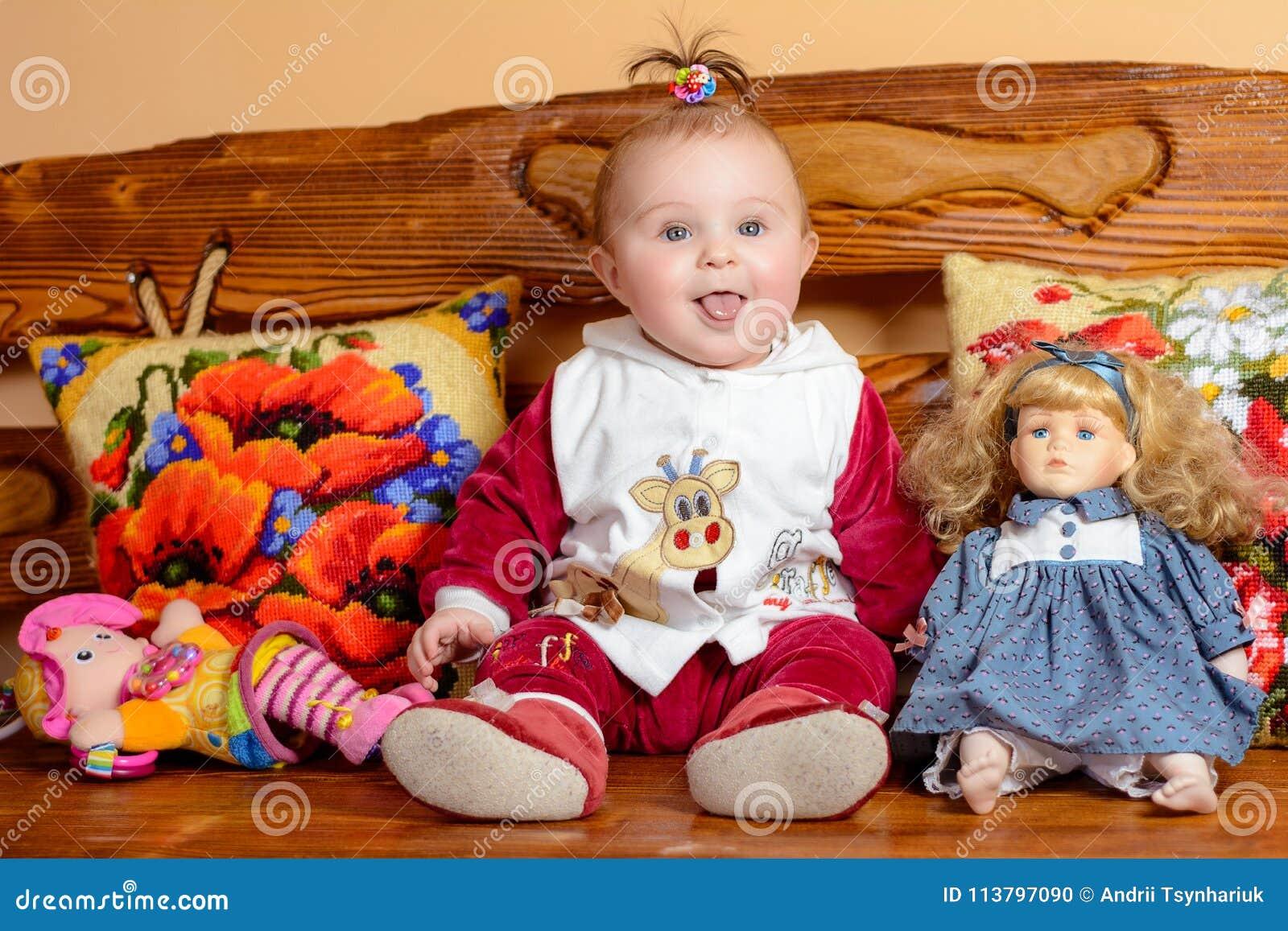 Mały dziecko z ogonem siedzi na kanapie z upiększonymi poduszkami i zabawkami