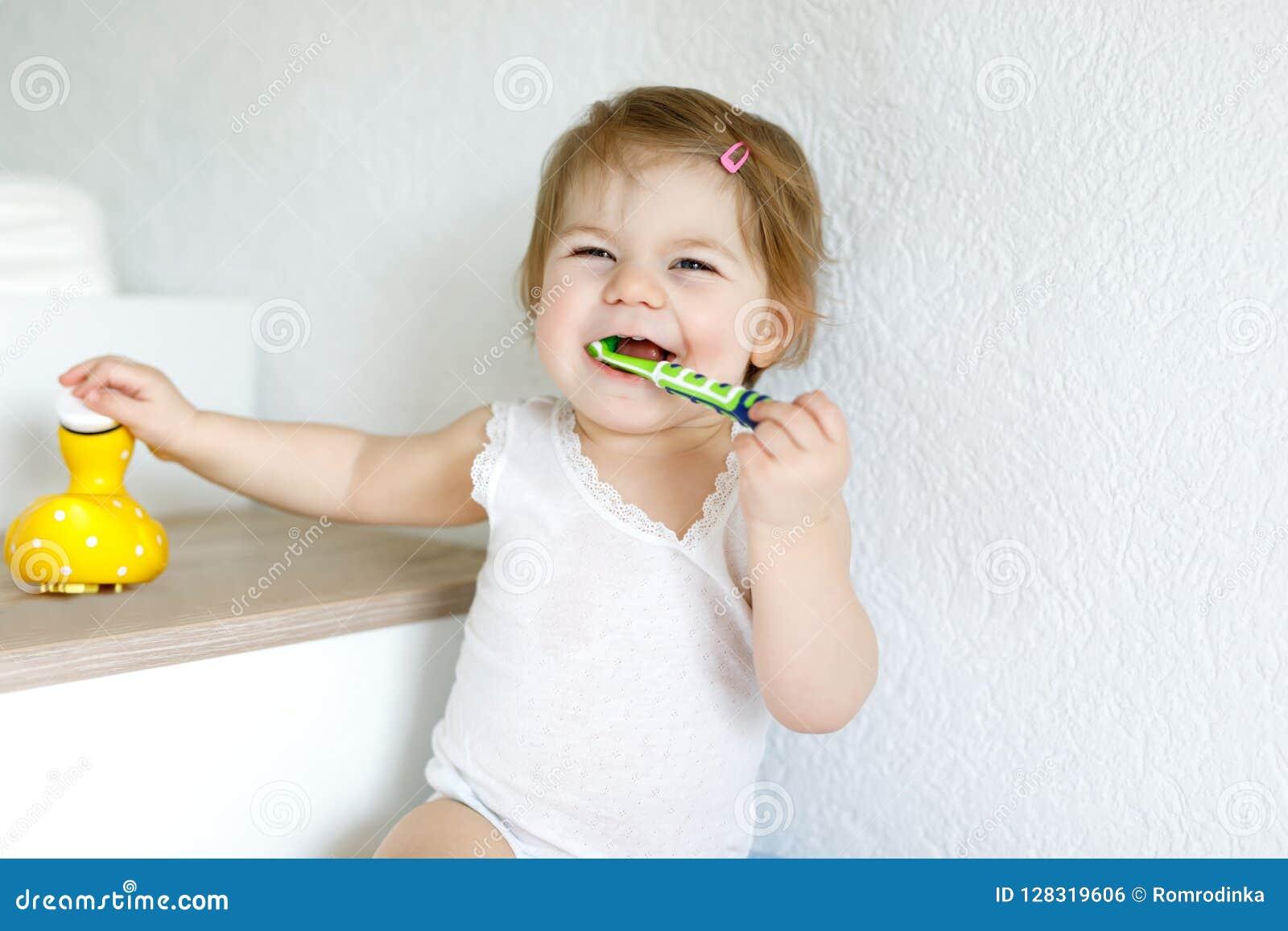 Mały dziewczynki mienia toothbrush i szczotkować pierwszy zęby Berbeć uczy się czyścić dojnego ząb