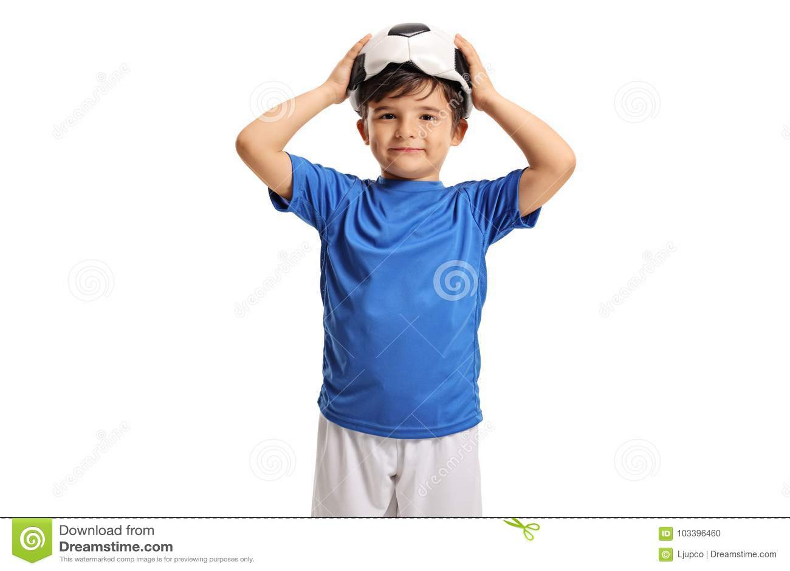Mały futbolista trzyma deflated futbol na jego głowie