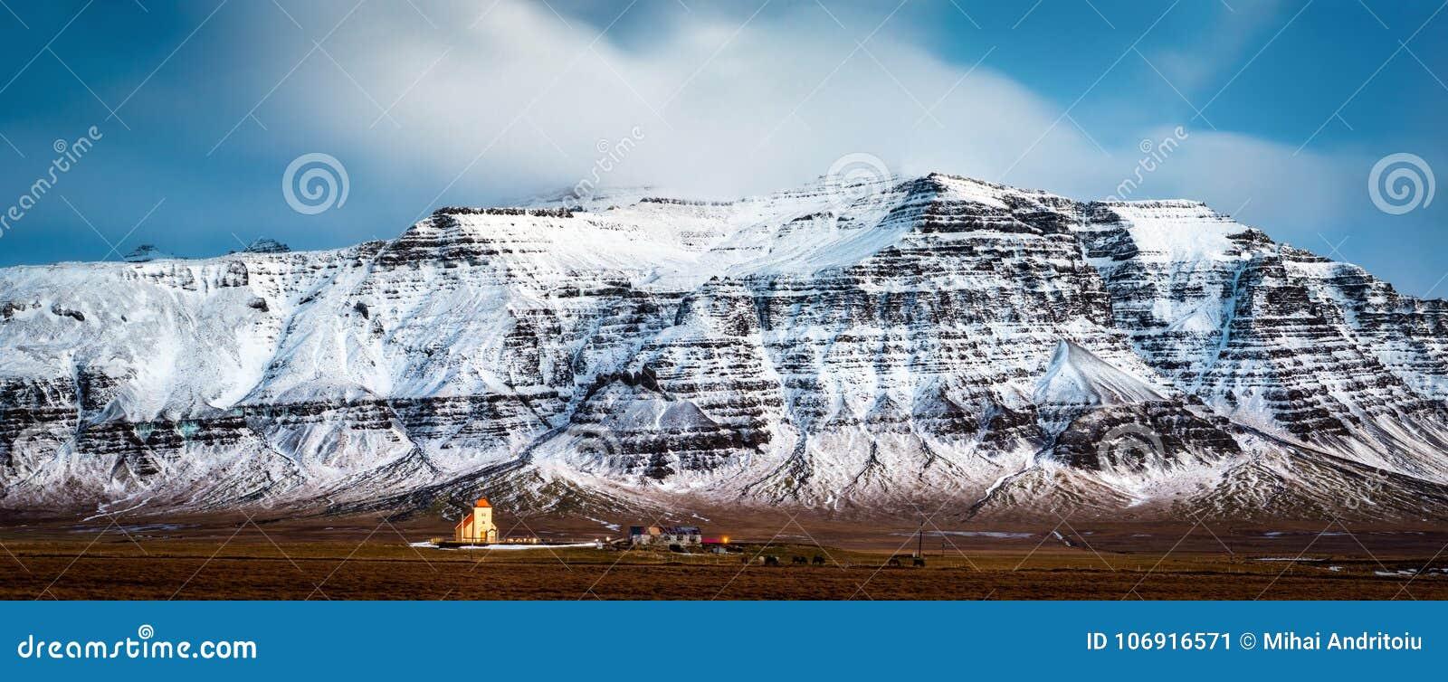 Mały icelandic kościół pod śnieg nakrywać górami