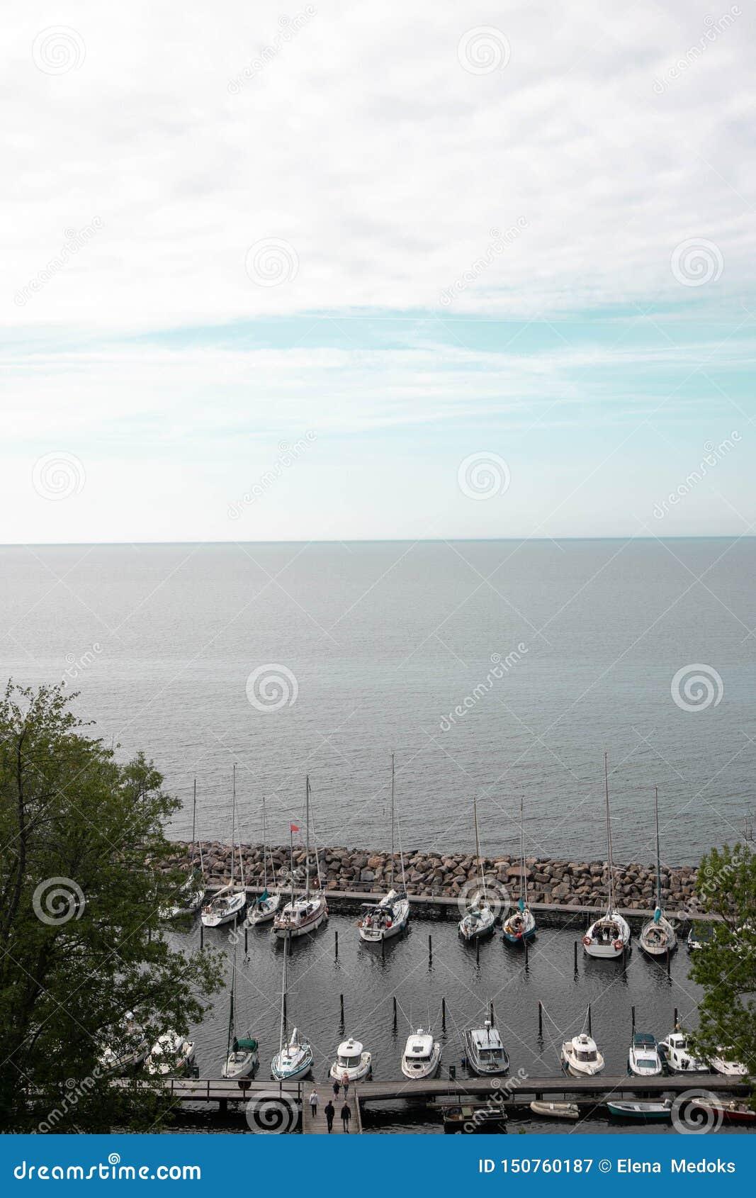Mały jetty dla intymnych łodzi Intymne łodzie i łodzie na molu w morzu przeciw niebieskiemu niebu Łowić motorowe łodzie przy