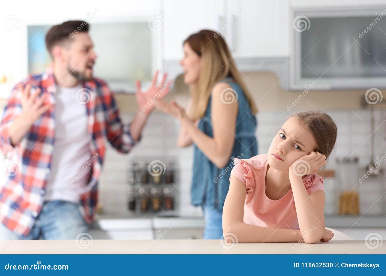 Mały nieszczęśliwy dziewczyny obsiadanie przy stołem podczas gdy rodzice
