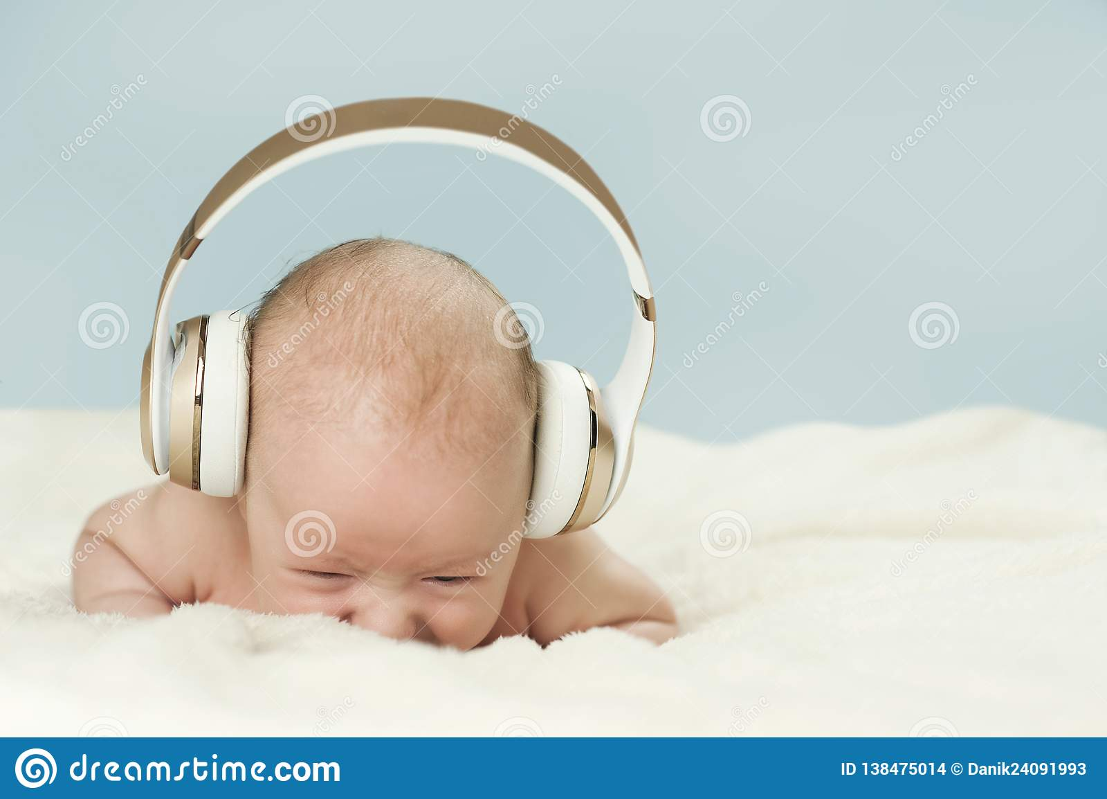 Mały piękny nowonarodzony dziecko słucha muzyka w dużych hełmofonach, odizolowywająca na błękitnym tle