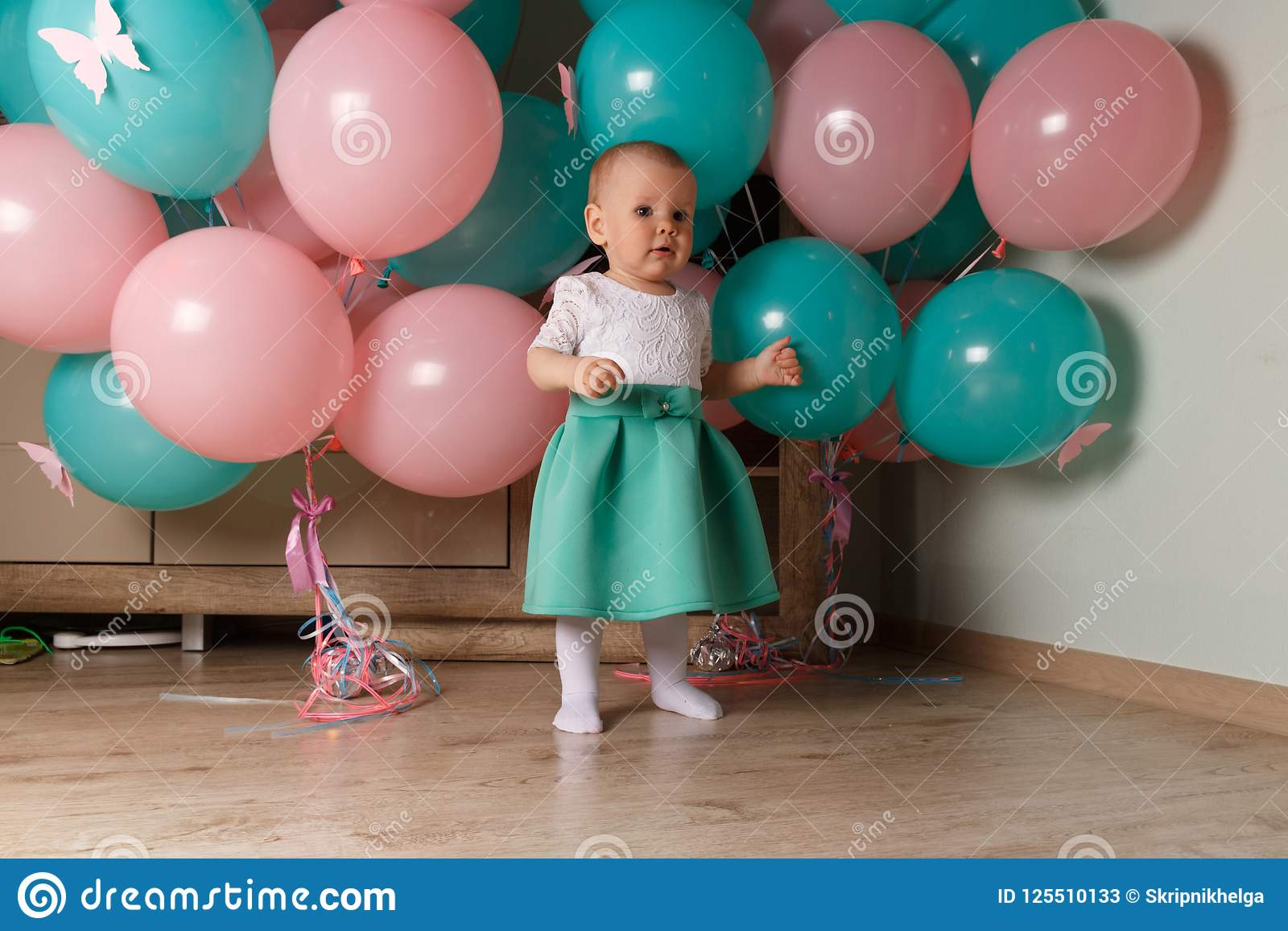 Mały, powabny dziecko, dziewczyna, świętuje jej pierwszy urodziny, siedzi obok ona z balonami Dziecka ` s Partyjna organizacja