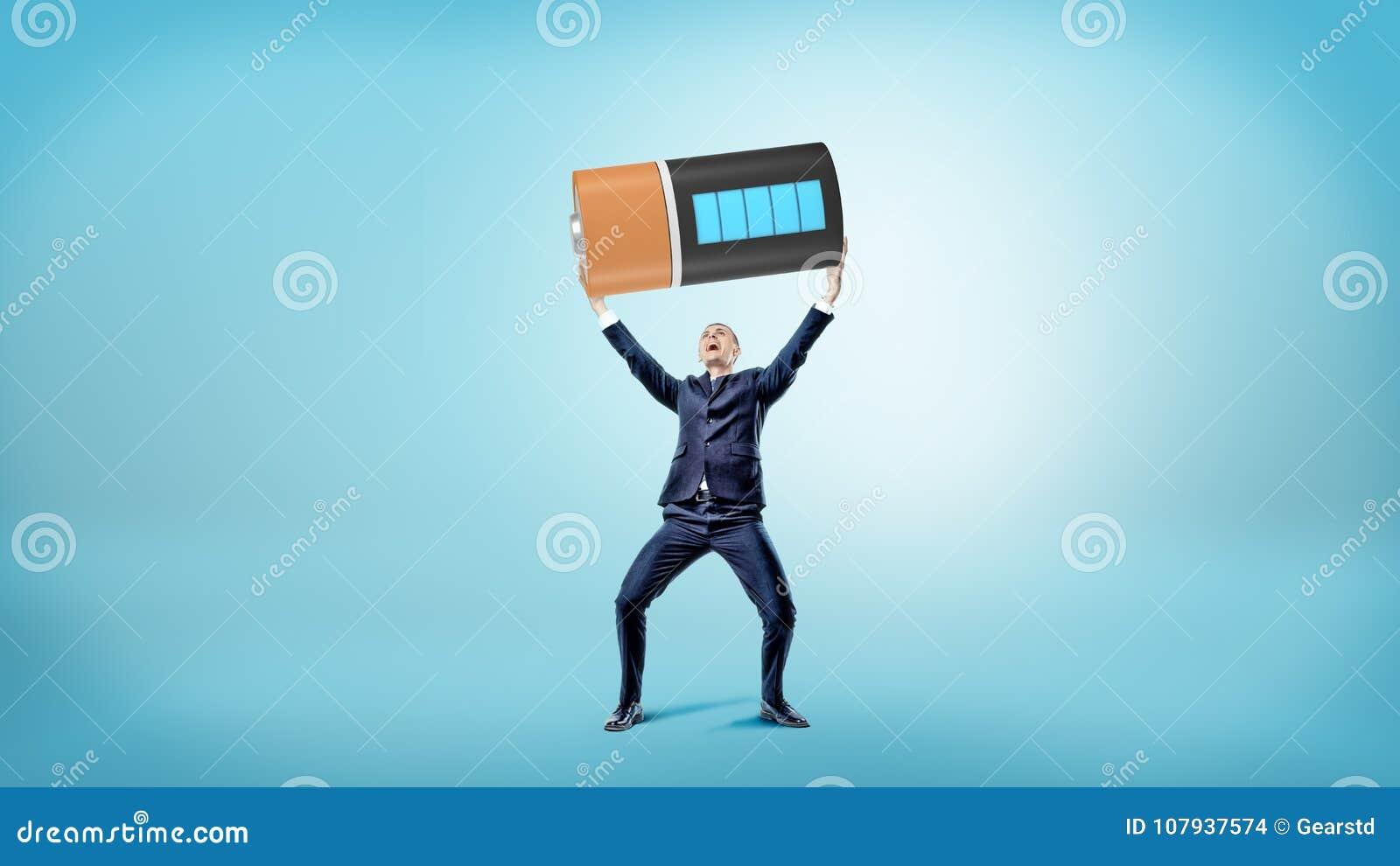 Mały szczęśliwy biznesmen uśmiecha się ogromną w pełni ładować baterię nad jego głową i trzyma