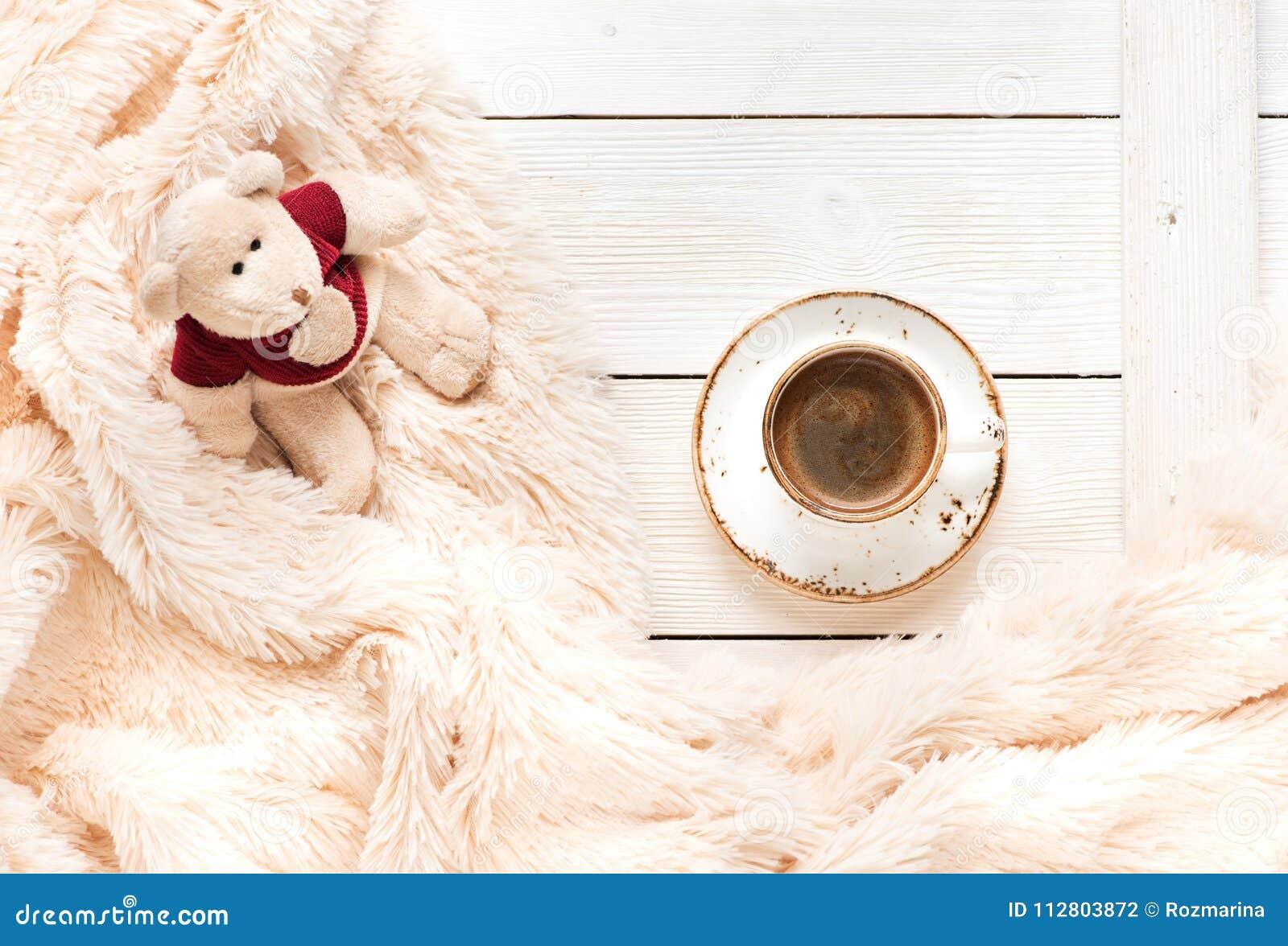 Mały trykotowy dziecko zabawki niedźwiedź siedzi na ciepłej koc i filiżance kawy