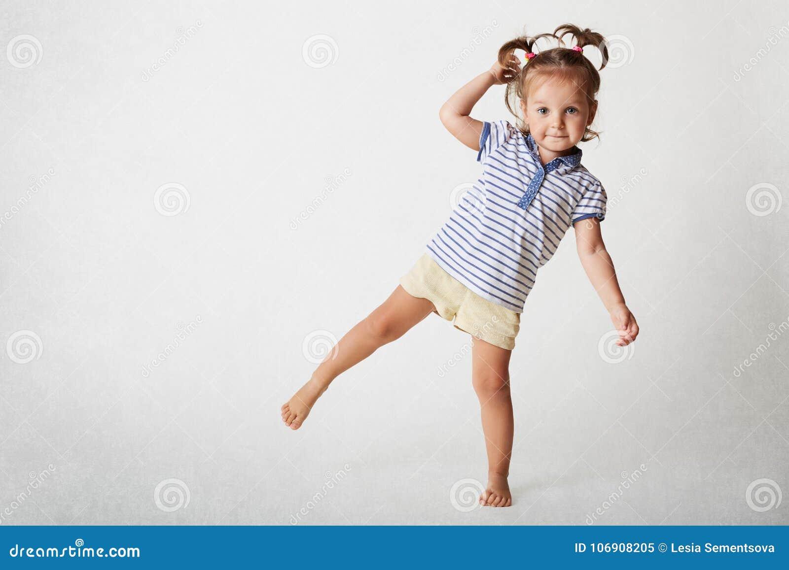 Mały uroczy żeński dziecko śmiesznego wyrażenie, jest ubranym casaul t koszula i zwiera, dwa konika ogonu, stojaki na jeden nodze