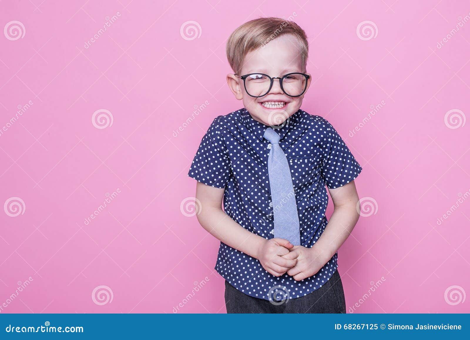 Mały uroczy dzieciak w krawacie i szkłach szkoła preschool Moda Pracowniany portret nad różowym tłem