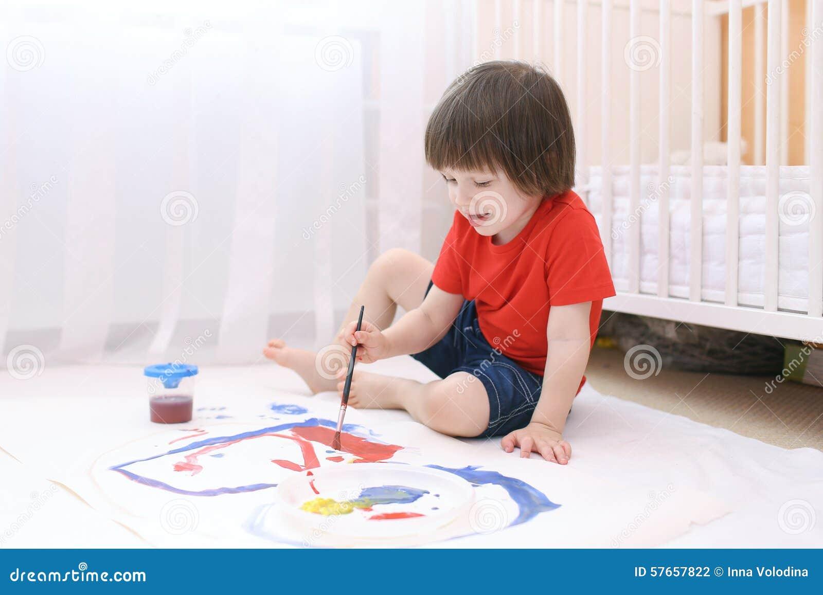Mały uroczy dziecko maluje z muśnięciem i guaszem