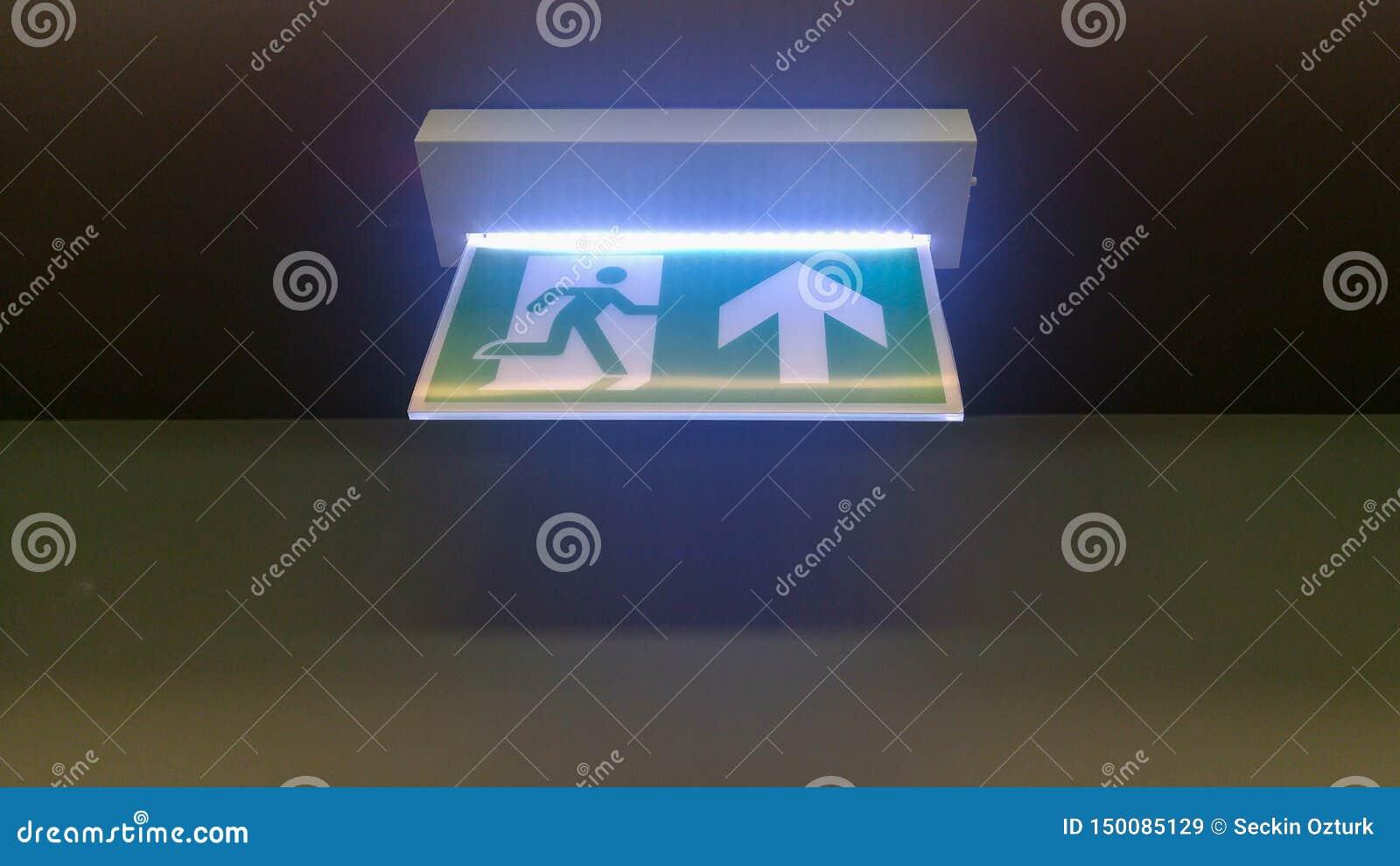 Mały zielony wyjście ewakuacyjne podpisuje wewnątrz biuro
