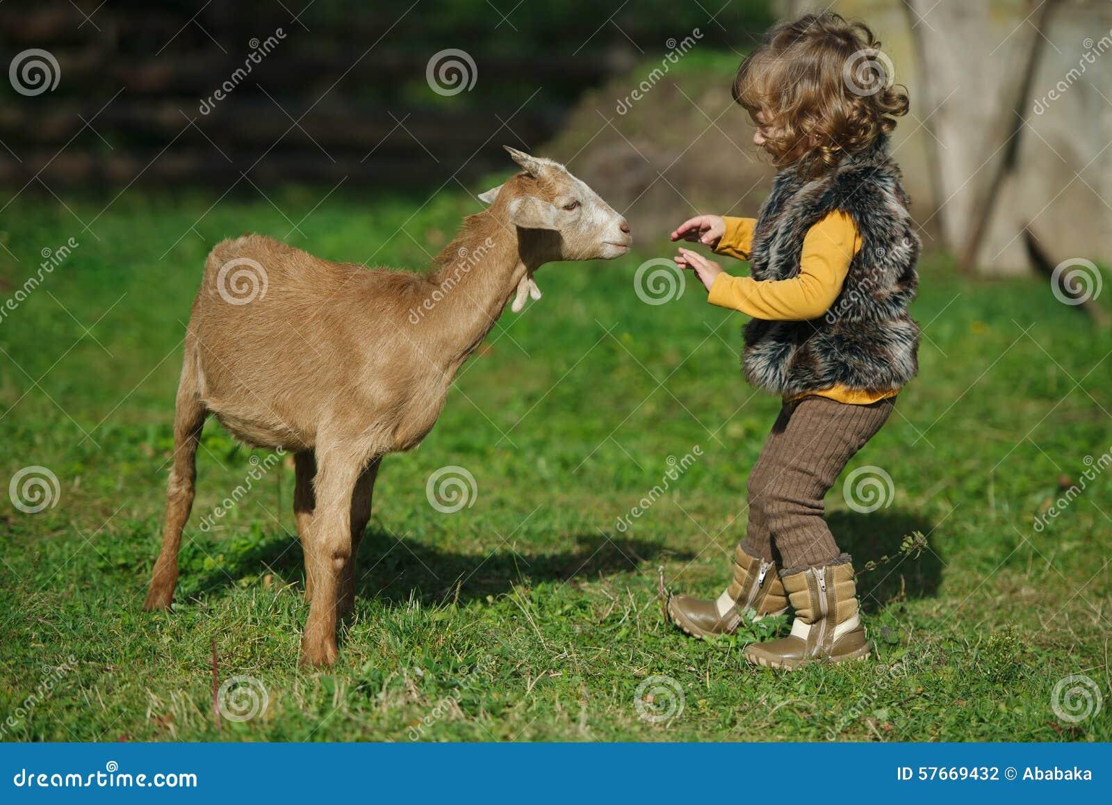 Małych dziewczynek sztuki z kózką na gospodarstwie rolnym
