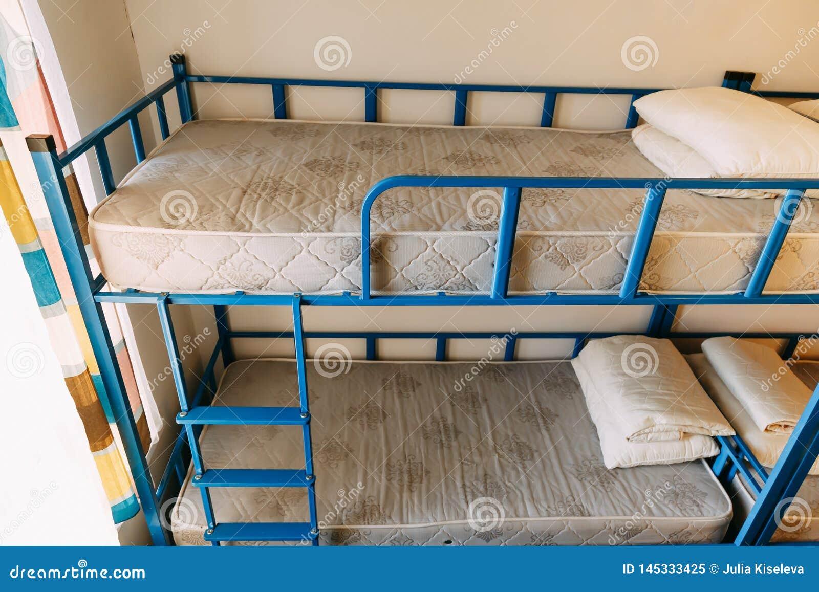 Ma?ana dentro del dormitorio del parador con las camas blancas limpias para los estudiantes y los turistas jovenes solos