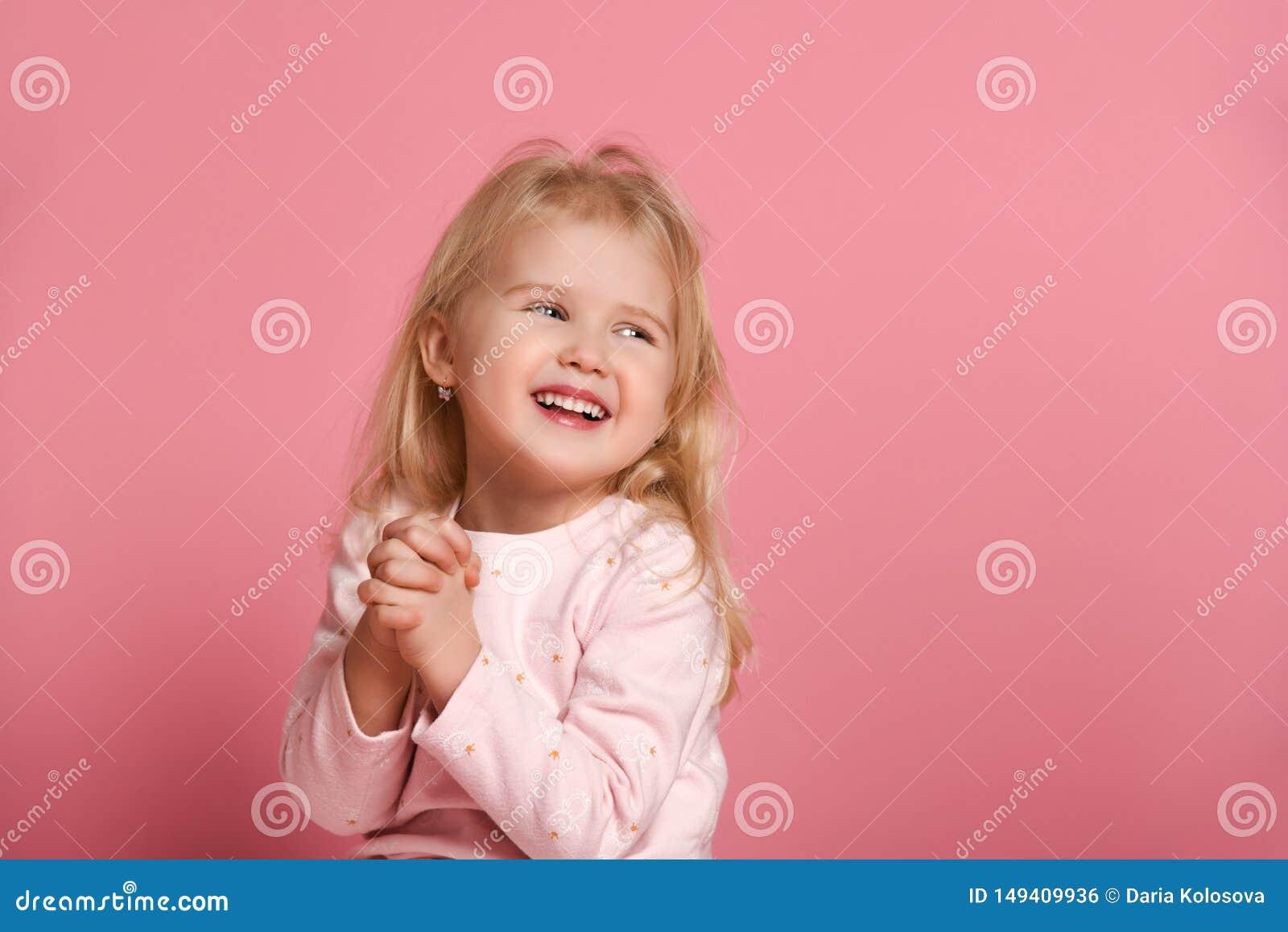Ma?a ?liczna dziewczyny dziecka blondynka w r??owym kostiumu jest nie?mia?a na r??owym tle