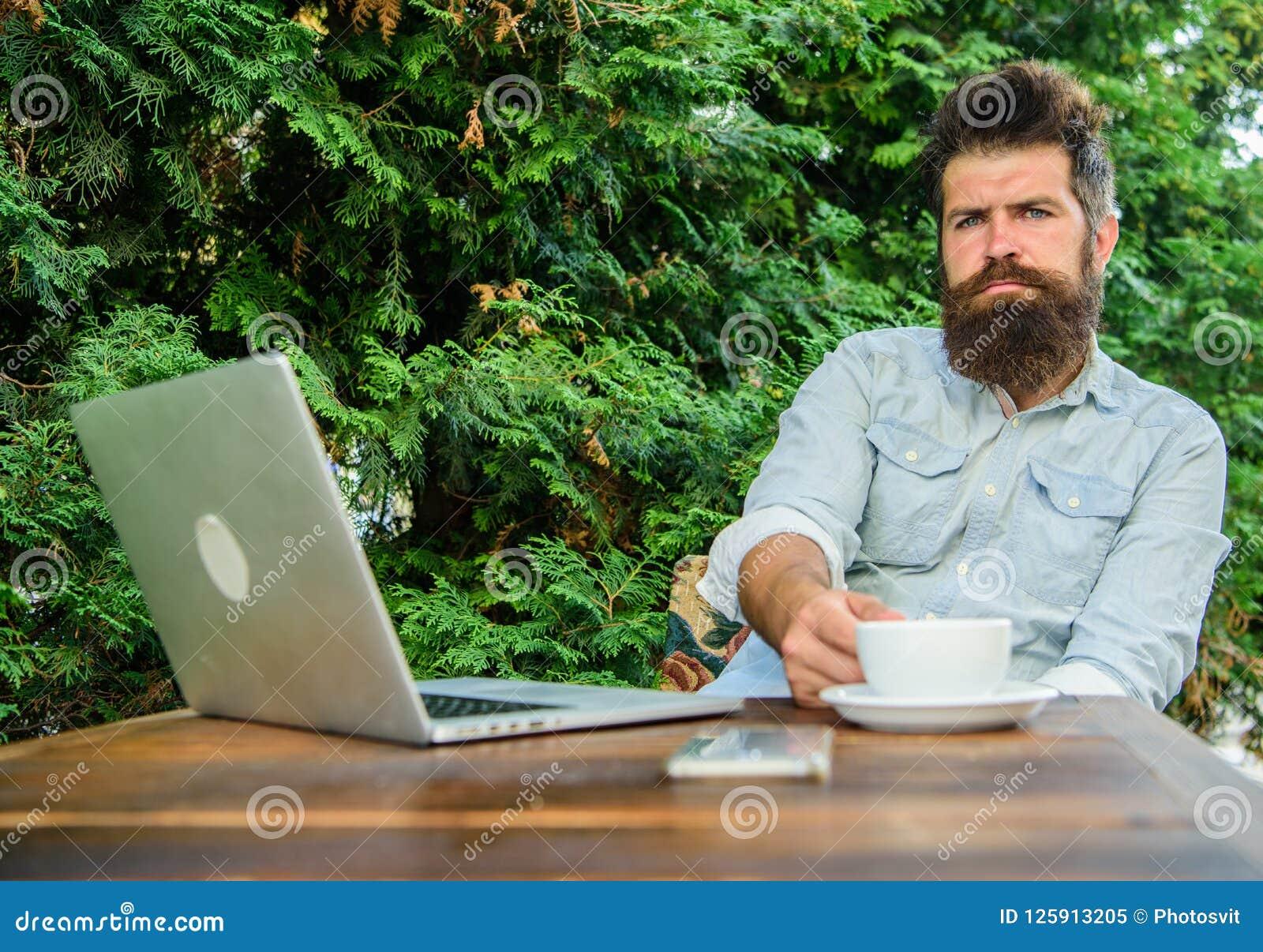 Maakt mensen gebaarde hipster pauze voor drinkt koffie en denkt terwijl met laptop zit Te ontspannen onderbreking De kerel drinkt