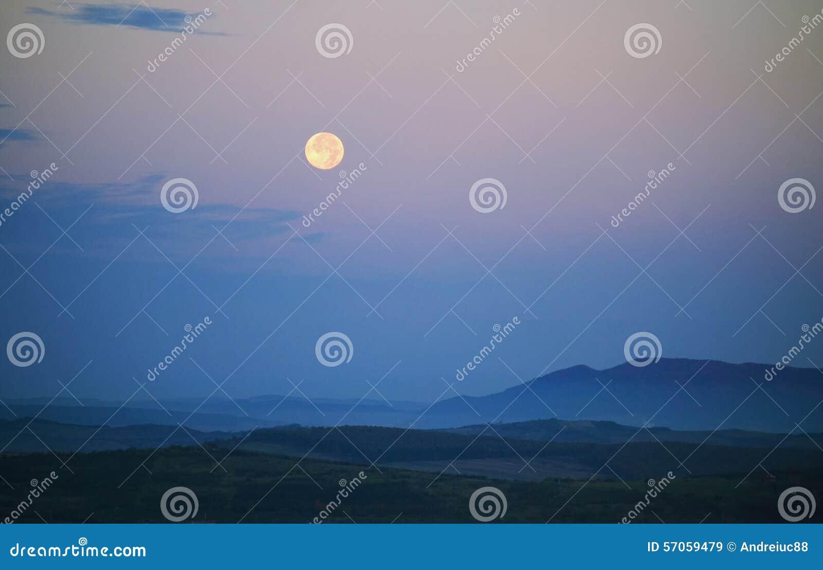 Maan die over berglandschap toenemen