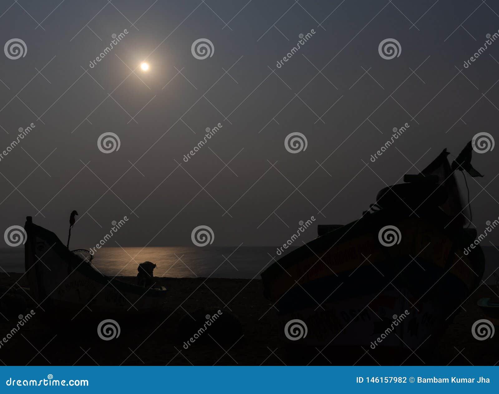 Maanlicht bij kust met de schaduw van de vissersboot