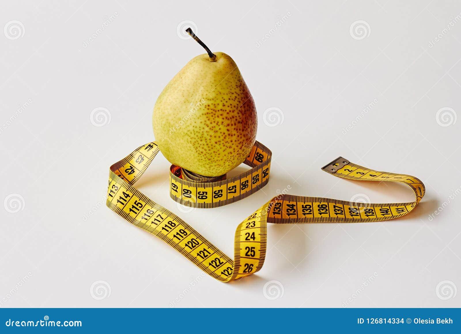 Maatregelenband en vers fruitpeer op witte achtergrond Verliesgewicht, slank lichaam, gezonde voedingconcept