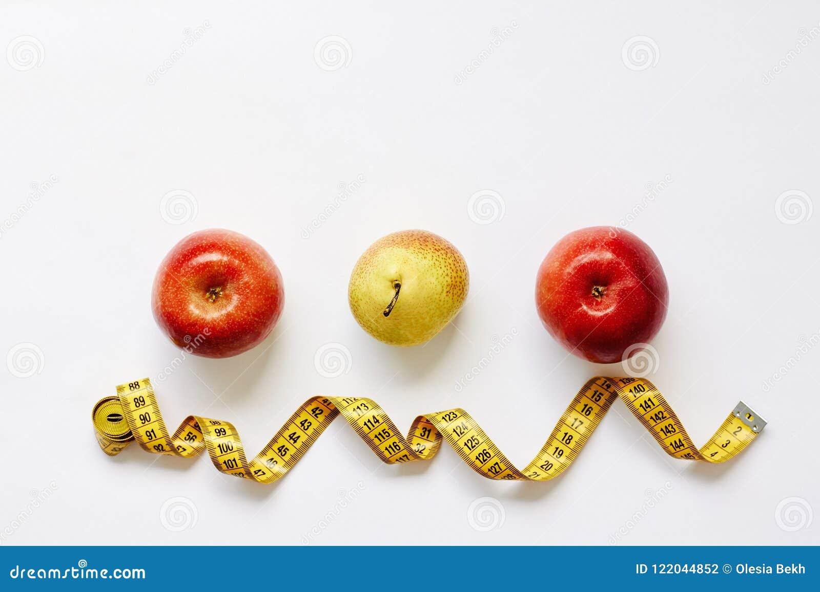 Maatregelenband en verse vruchten appelen, peer op witte achtergrond Verliesgewicht, slank lichaam, gezonde voedingconcept