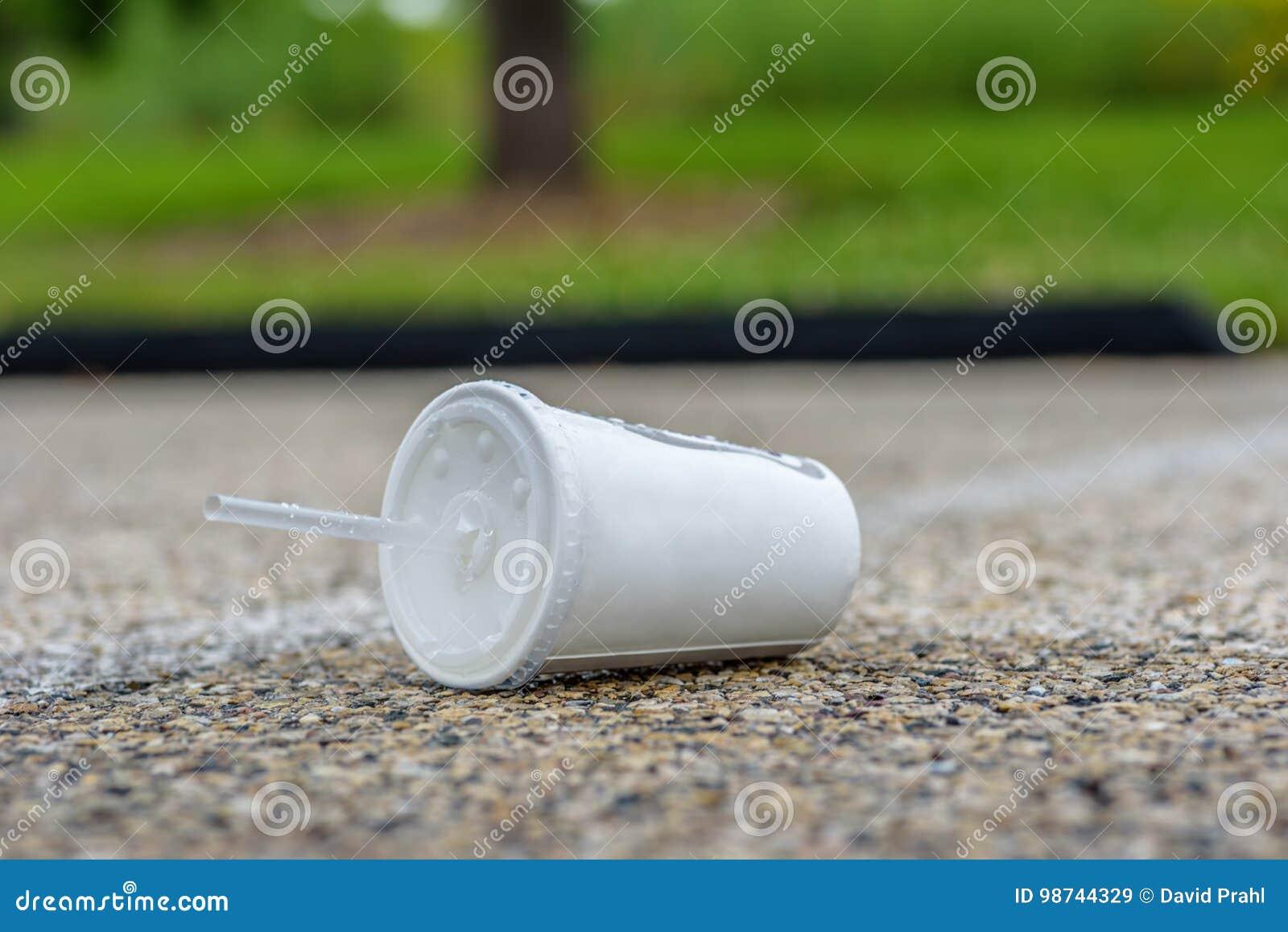 Maca do copo do refresco no pavimento