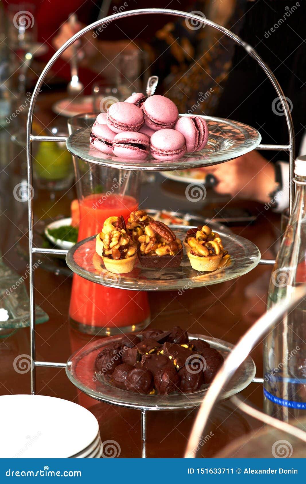 Macaron, mandcakes en chocolade die op een speciale tribune liggen