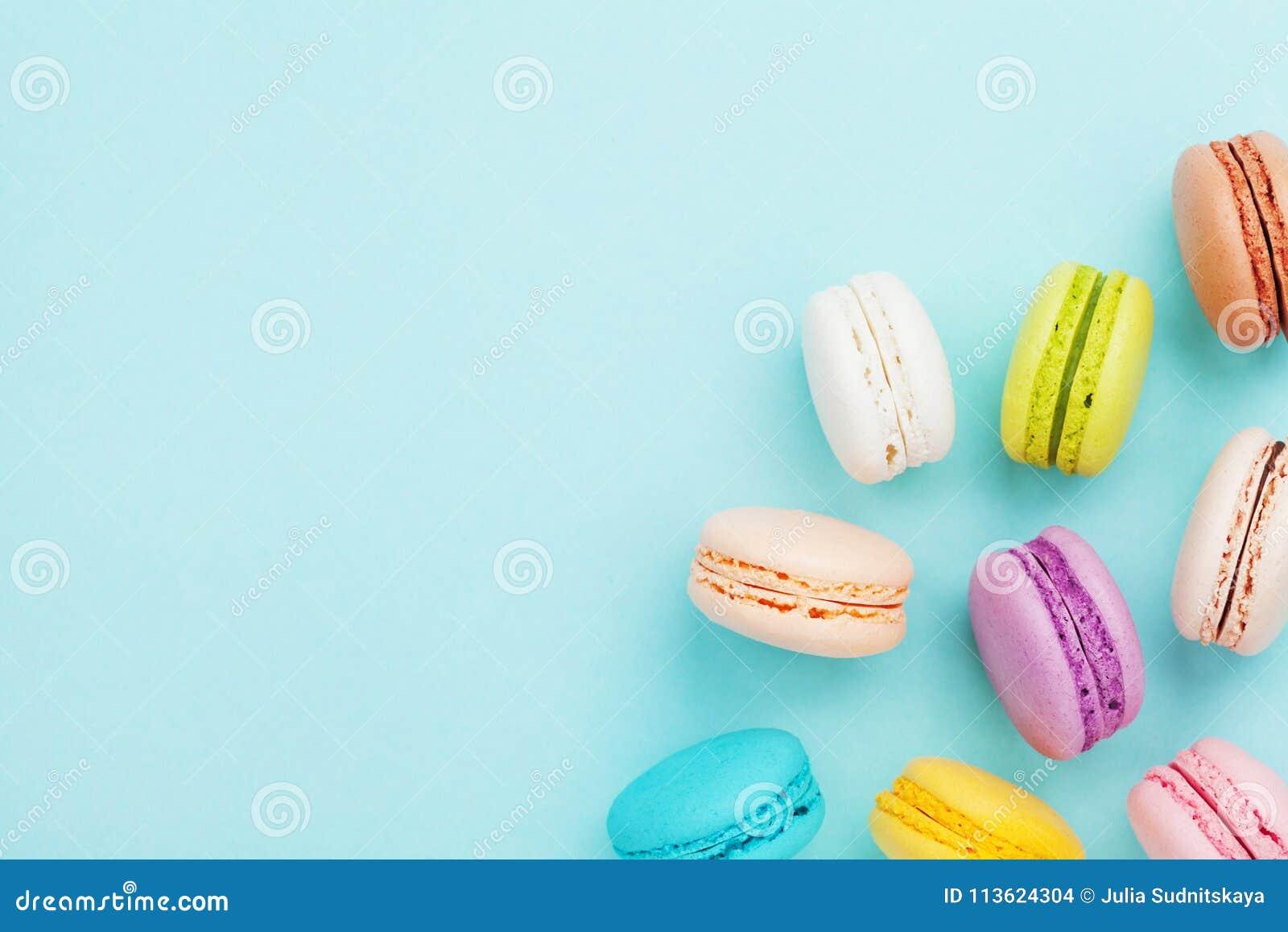 Macaron ou macaron savoureux de gâteau sur le fond en pastel de turquoise d en haut Biscuits français colorés sur la vue supérieu