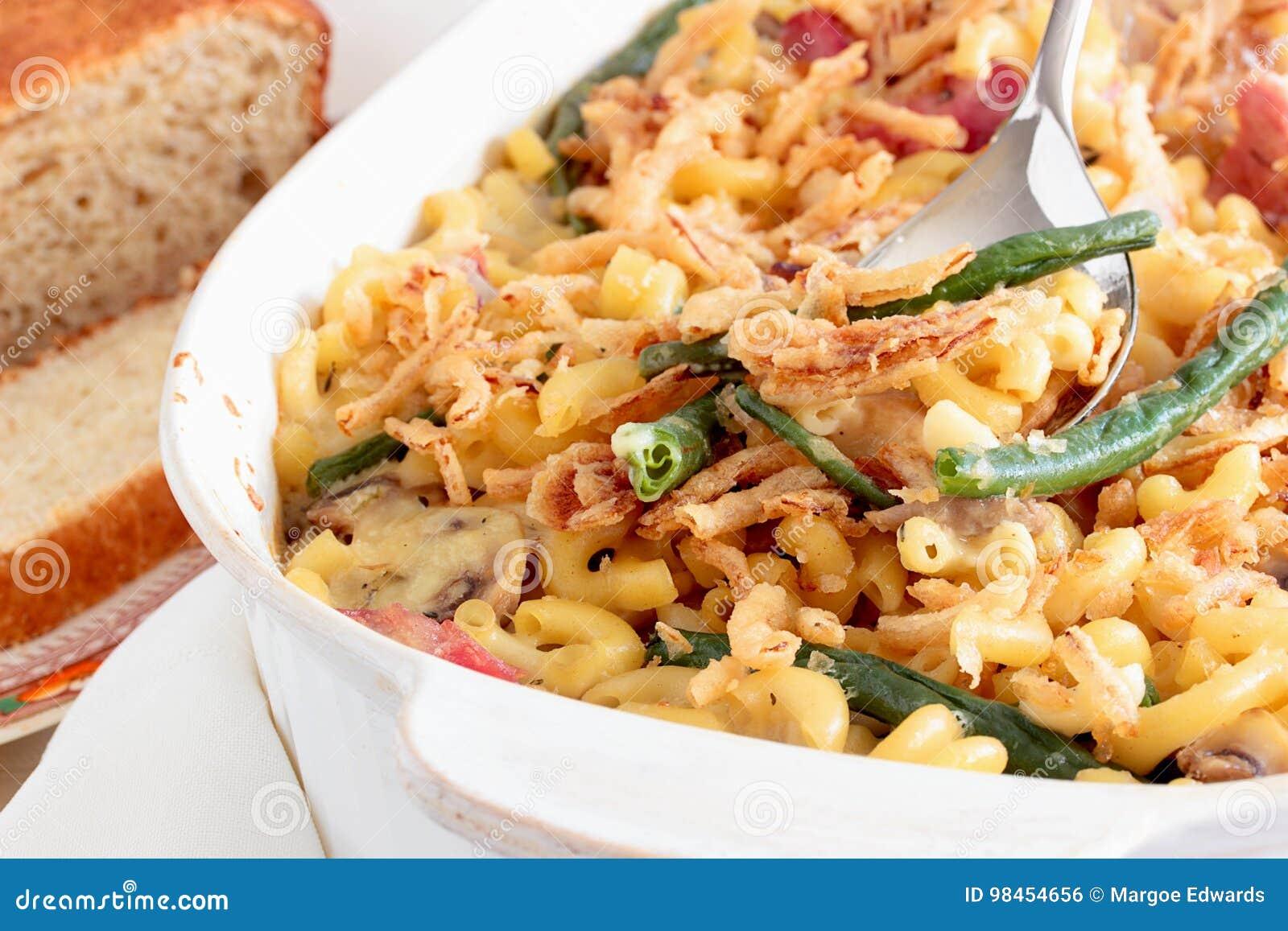 Macaroni en kaasbraadpan met gebraden uiringen die wordt bedekt