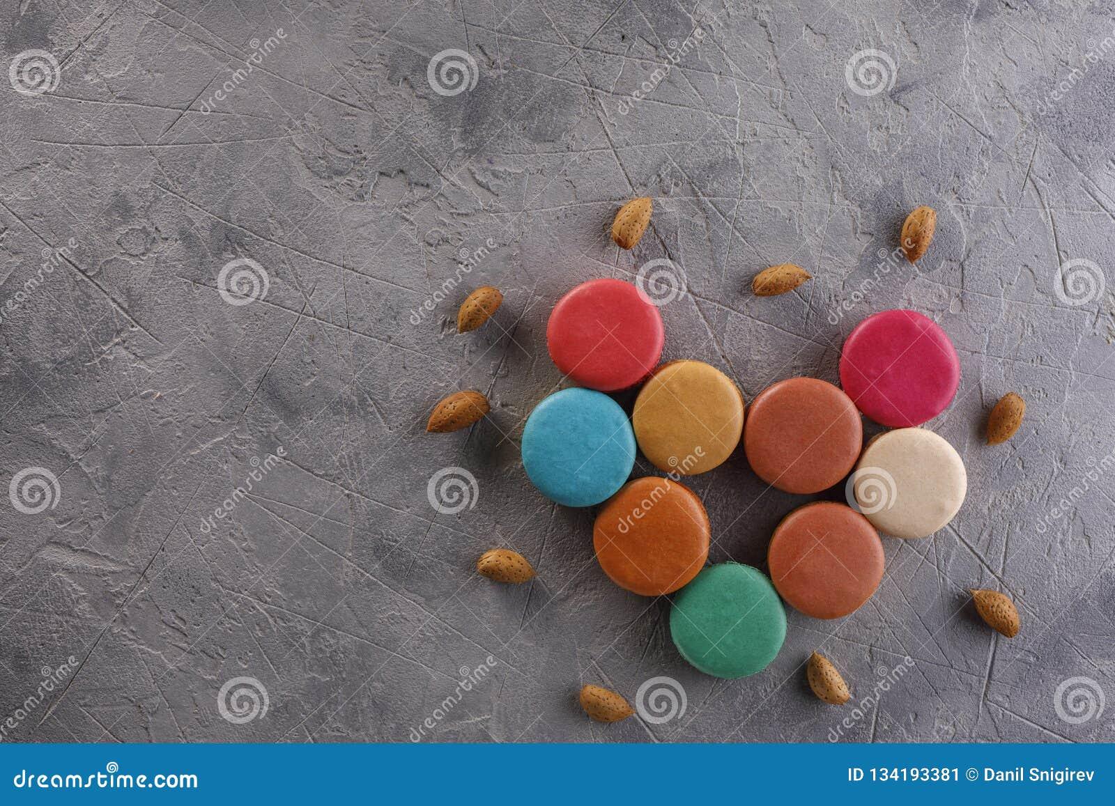 Macarons apresentou sob a forma das porcas do coração e da amêndoa em um fundo estrutural Configuração lisa Conceito da nutrição