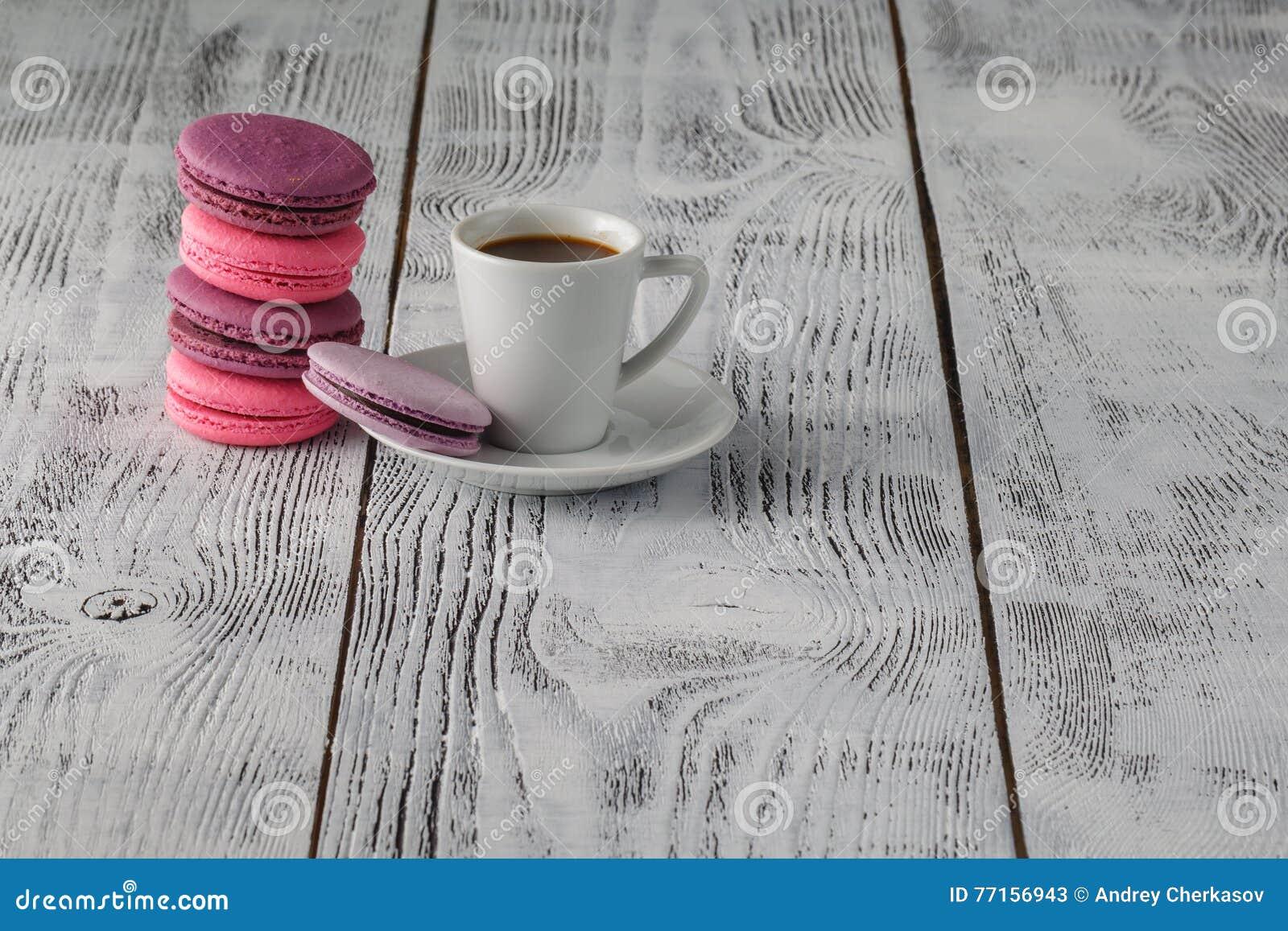 Macarons avec la tasse de café sur le fond en bois