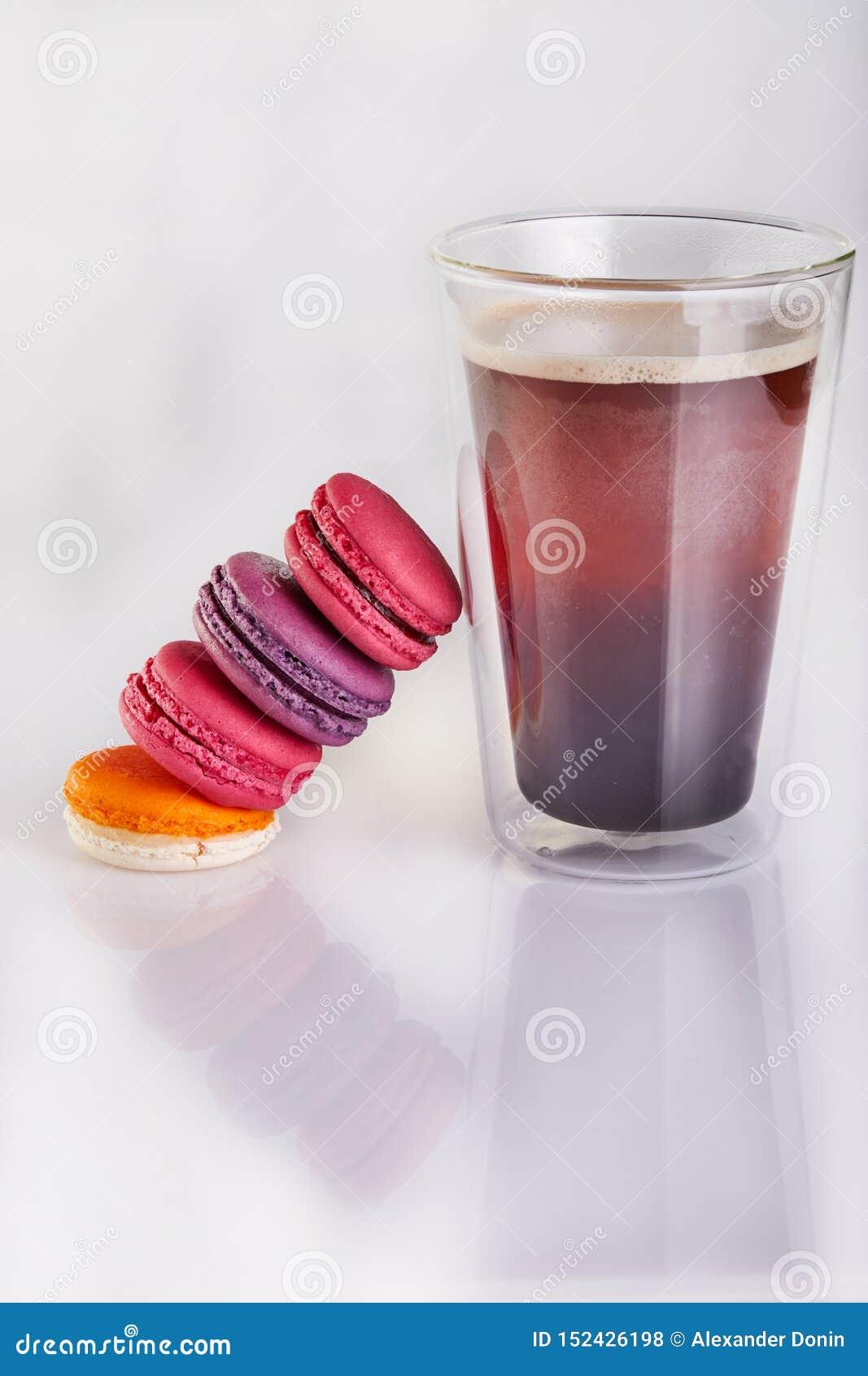 Macarons frais de différentes couleurs et saveurs et un verre de café d expresso sur un fond blanc