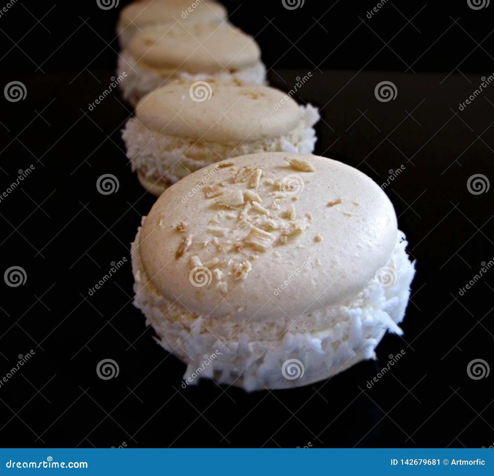 Macarons franceses del coco en fondo negro