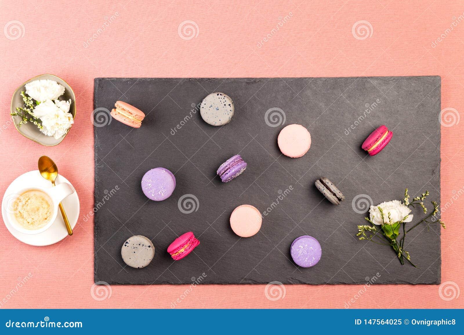 Macarons o macarrones franceses, y flor blanca de la encarnación en una pizarra, con café y flores blancas de las encarnaciones e