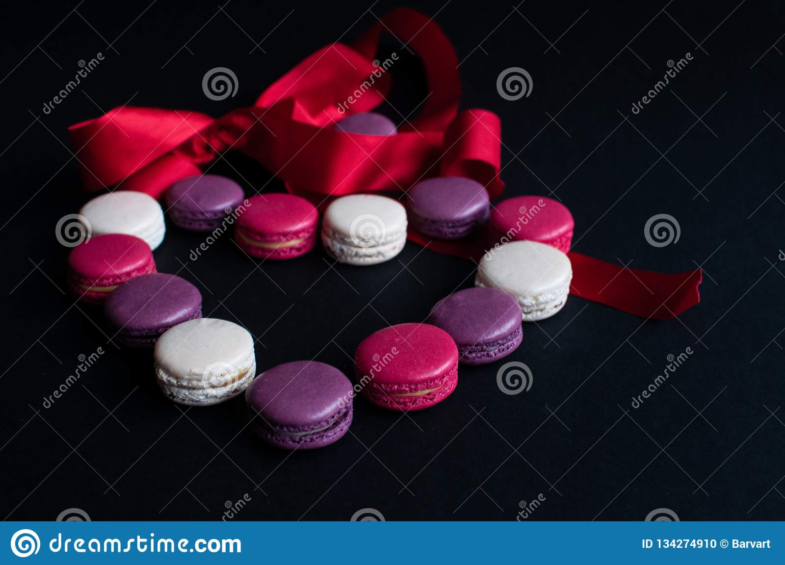 Macaroon laid out on a black background in the form of a heart with red ribbon. colorful almond cookies, pastel colors. Present