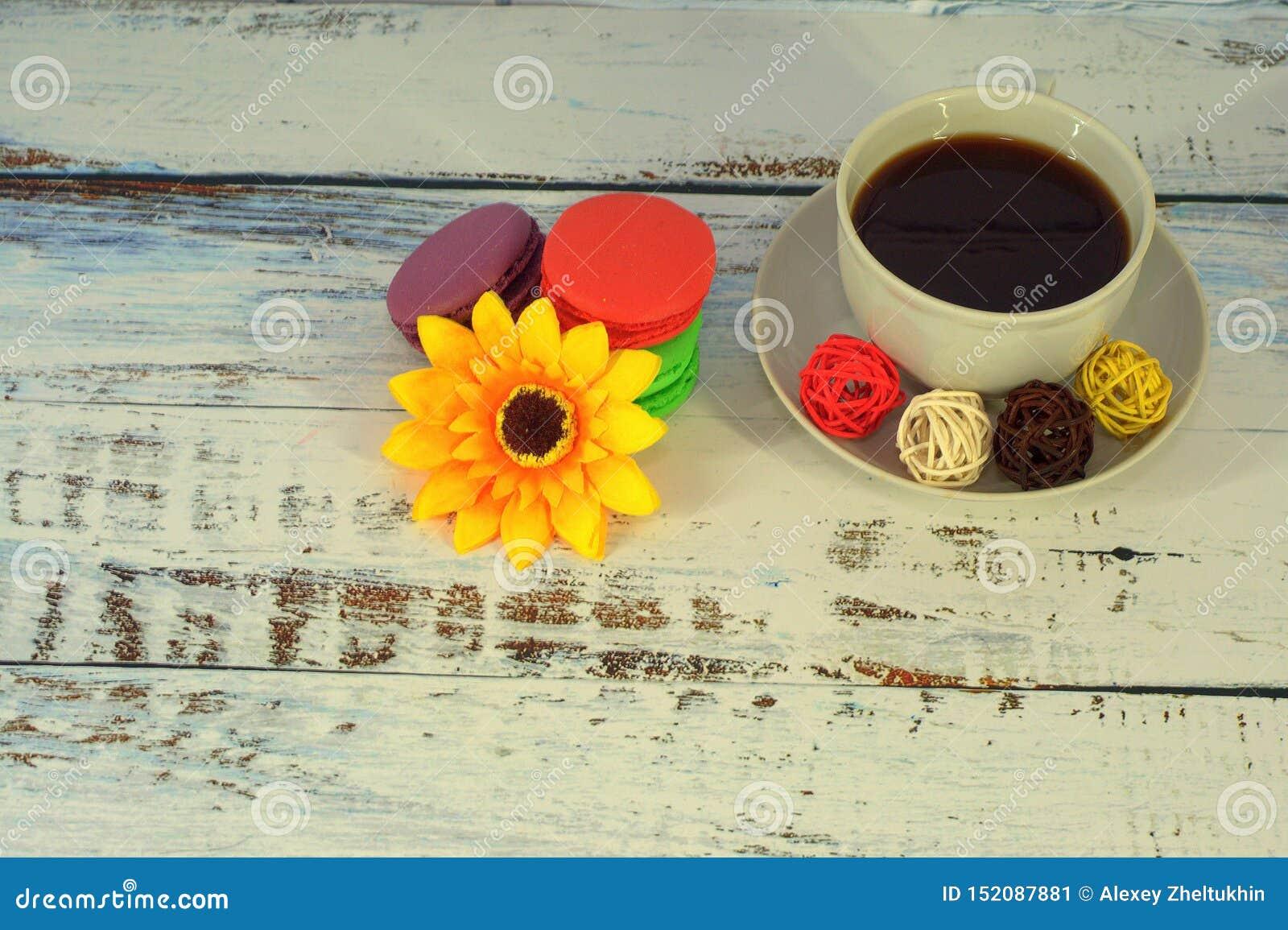 Macaroons, кофе, Баалы и цветок на таблице