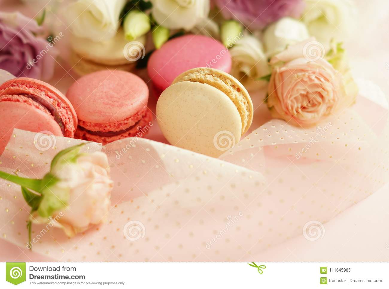 Macaroons in pastel colors with flowers on a pale pink background.Holiday background