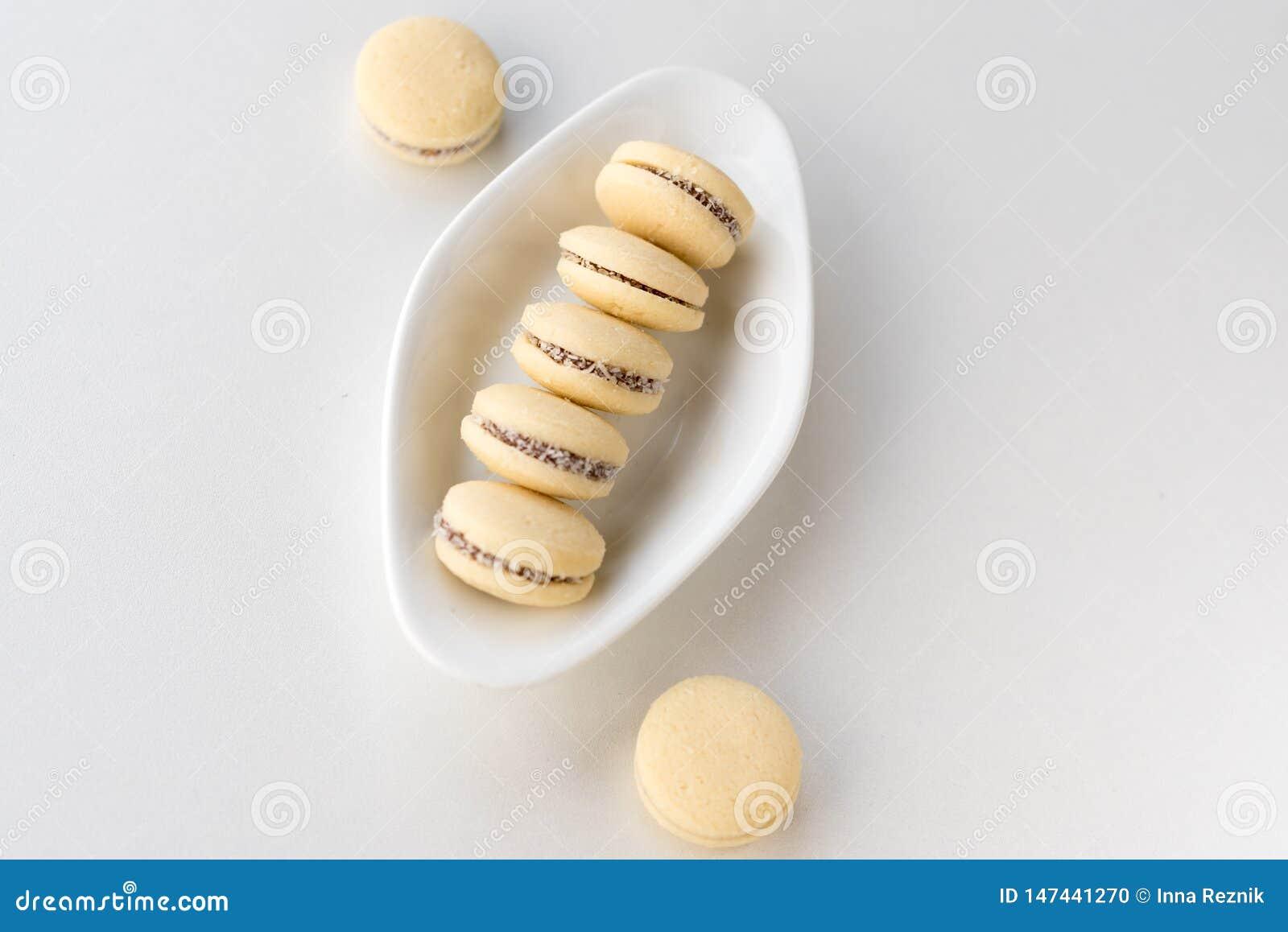 Macarrones blancos de la vainilla en fondo de madera Alfajores argentinos deliciosos de las galletas con crema en la placa Visi?n