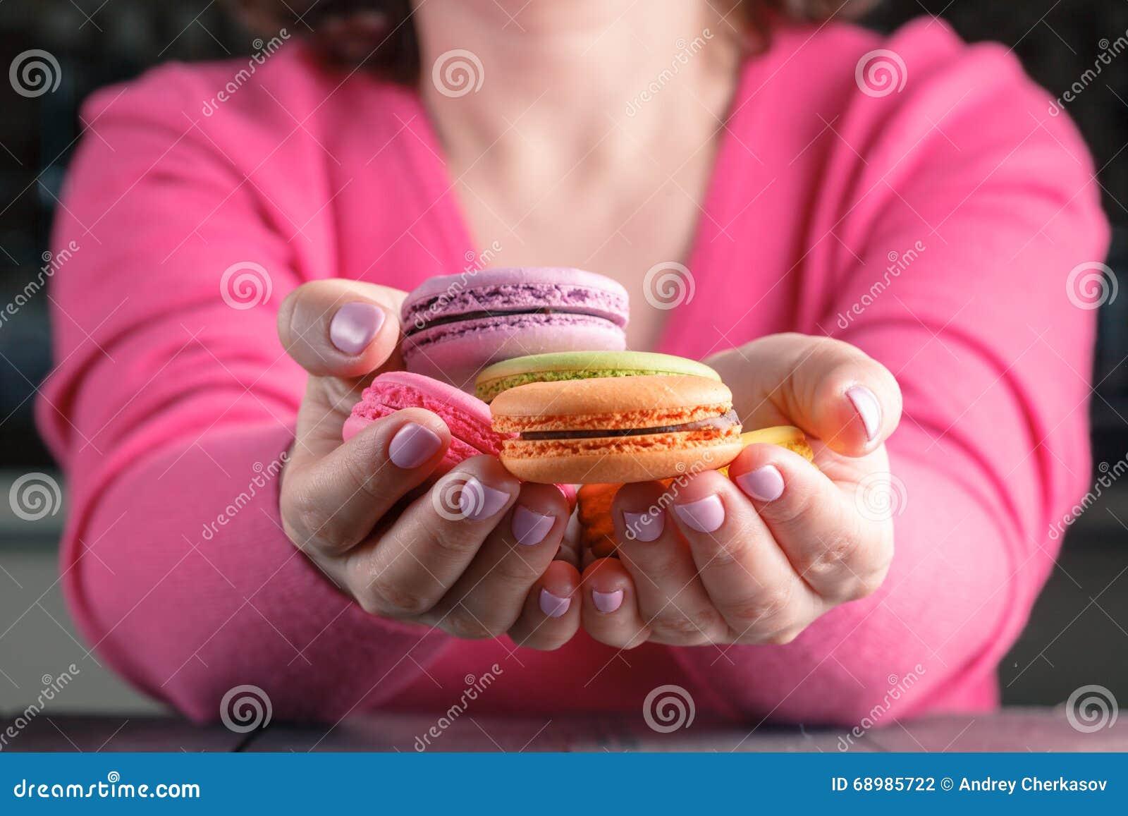 Macarrones coloreados en las manos de la mujer Pudín francés de la pasta de azúcar del chocolate Cierre-u