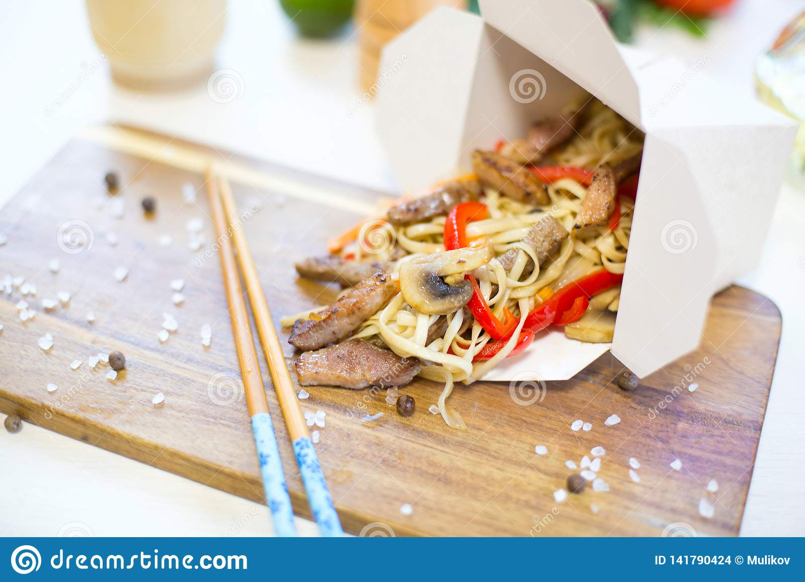 Macarronetes com carne de porco e vegetais na caixa para viagem na tabela de madeira