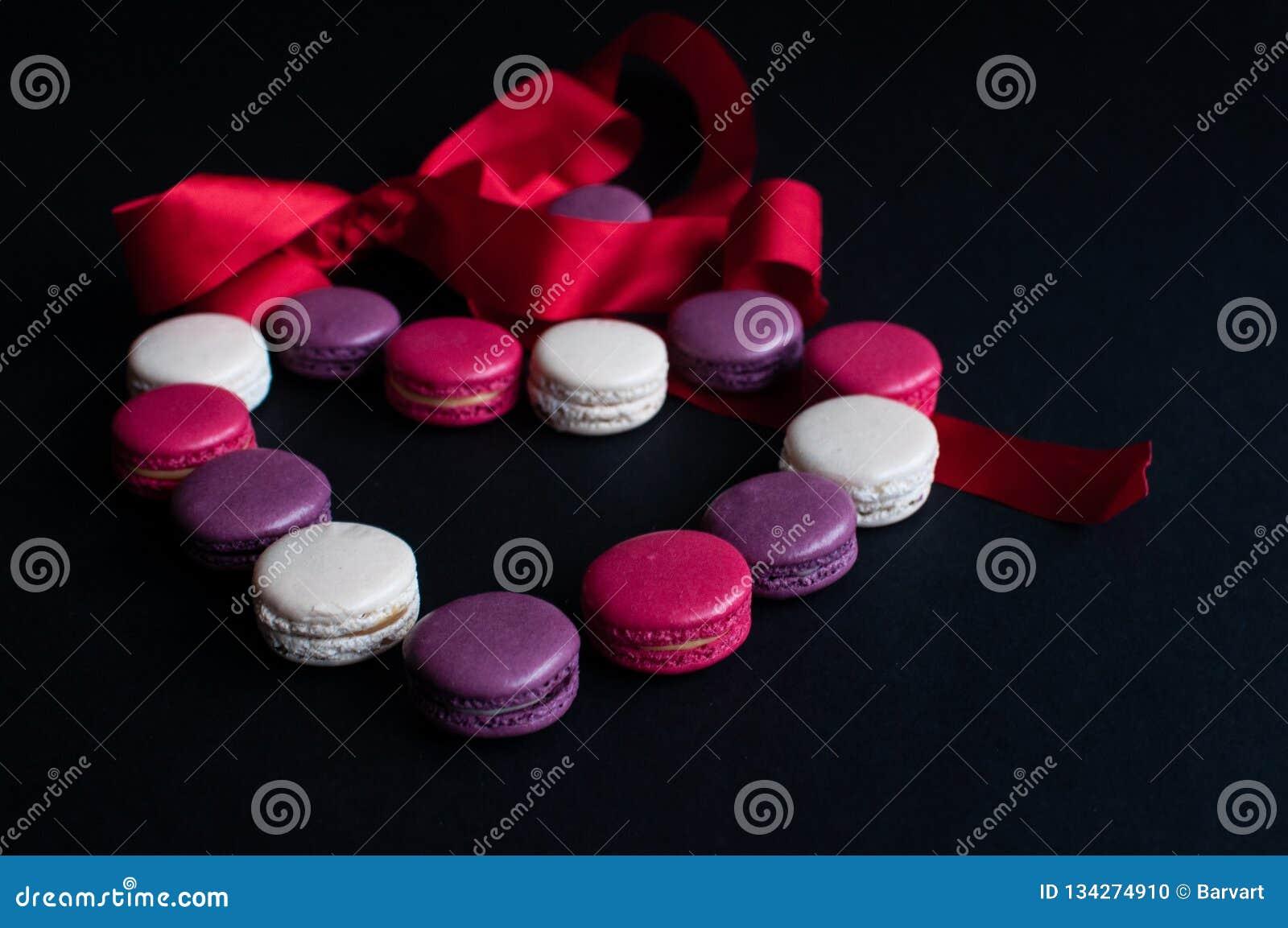 Maccherone presentato su un fondo nero sotto forma di cuore con il nastro rosso Biscotti di mandorla variopinti, colori pastelli