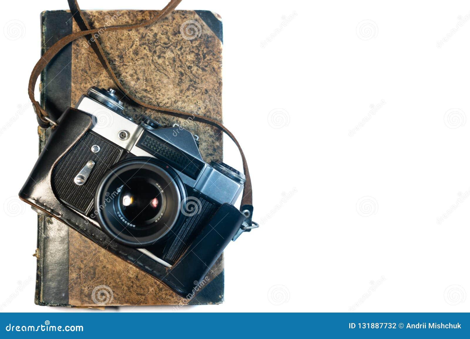 Macchina fotografica della foto e vecchio libro su fondo bianco isolato