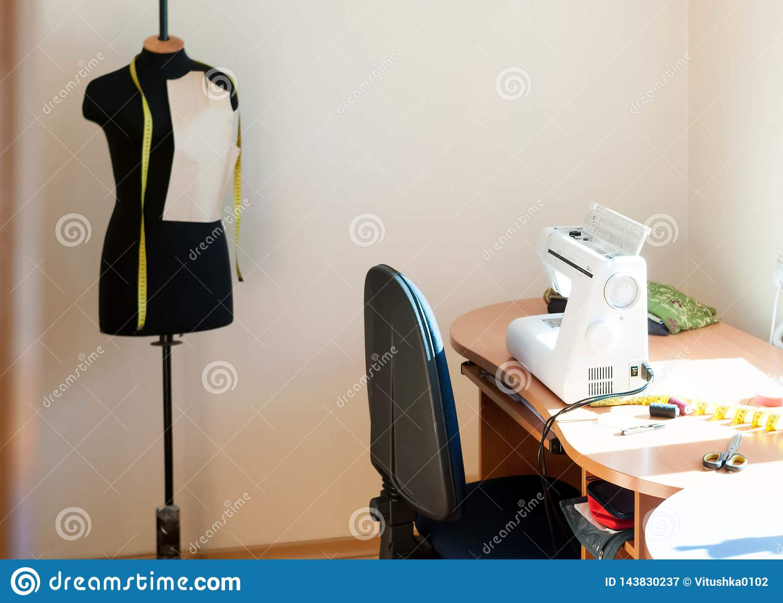 Macchina per cucire bianca, sedia blu, manichino nero con nastro adesivo