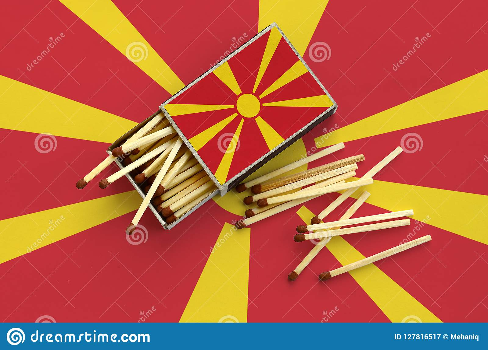 Macedonia flag is shown on an open matchbox, from which several matches fall and lies on a large flag