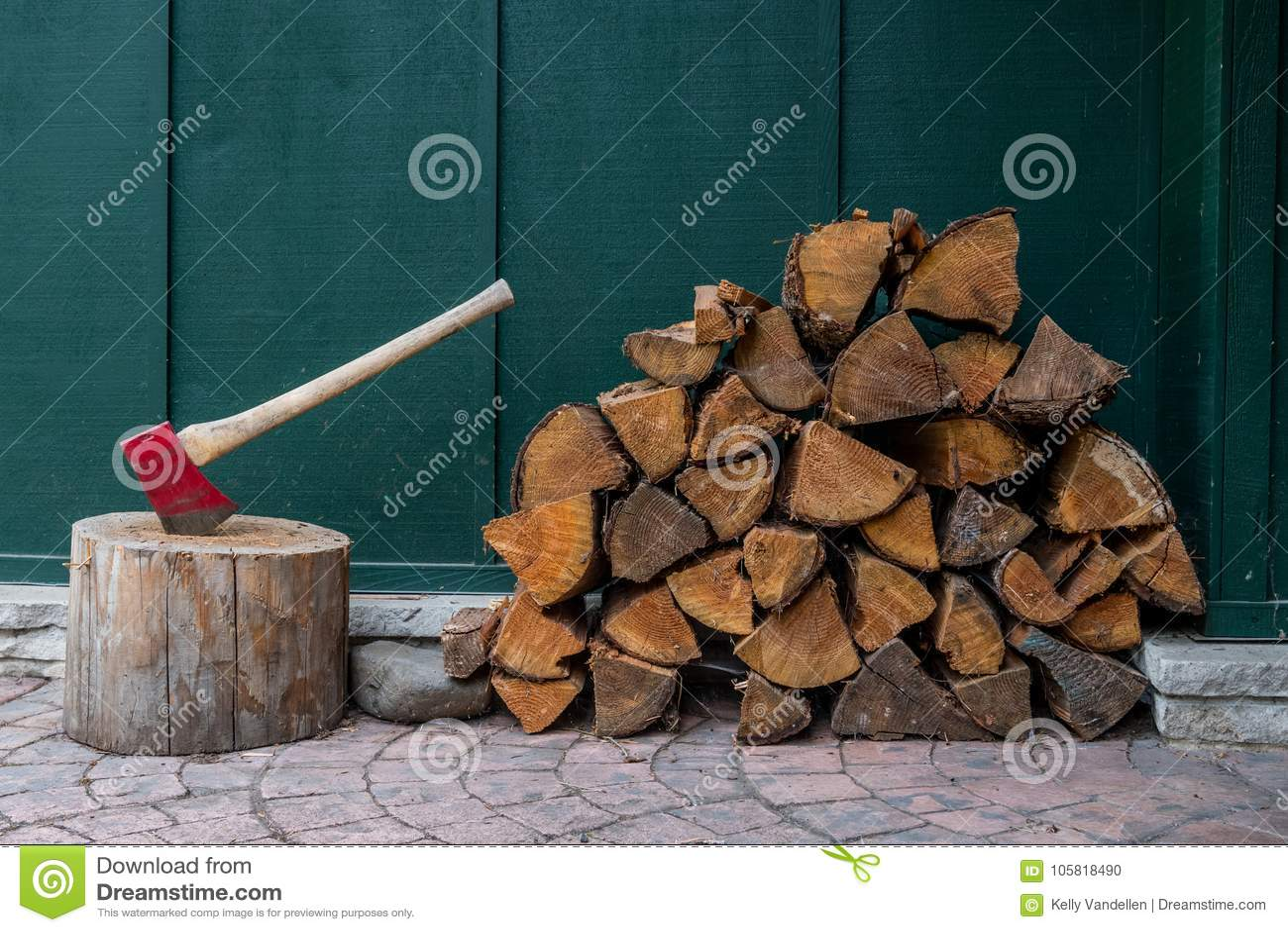 Machado e pilha vermelhos da madeira do fogo