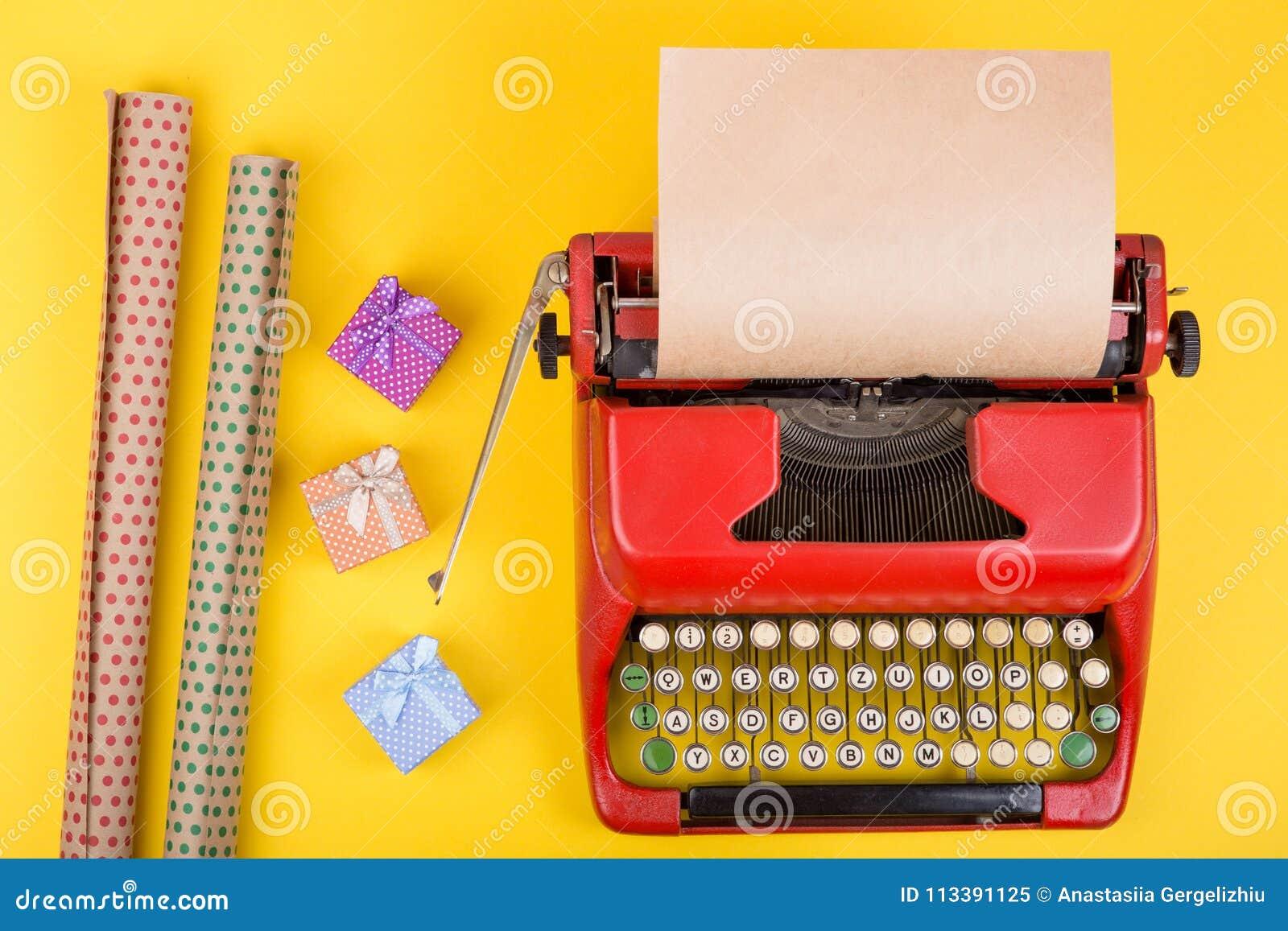 Machine à écrire rouge avec le papier vide de métier, boîte-cadeau sur le fond jaune