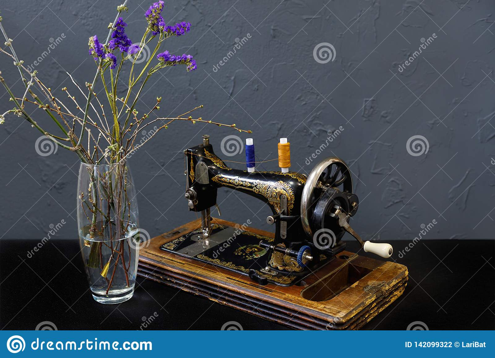 Machine à coudre de cru un vase avec les fleurs bleues