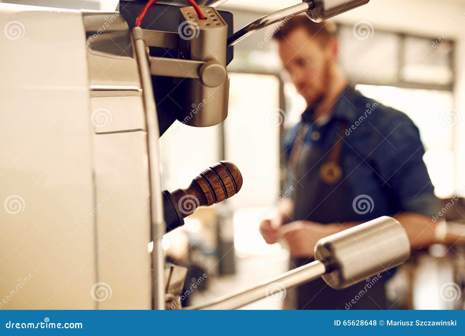Machine de torréfaction de grain de café avec l homme à l arrière-plan