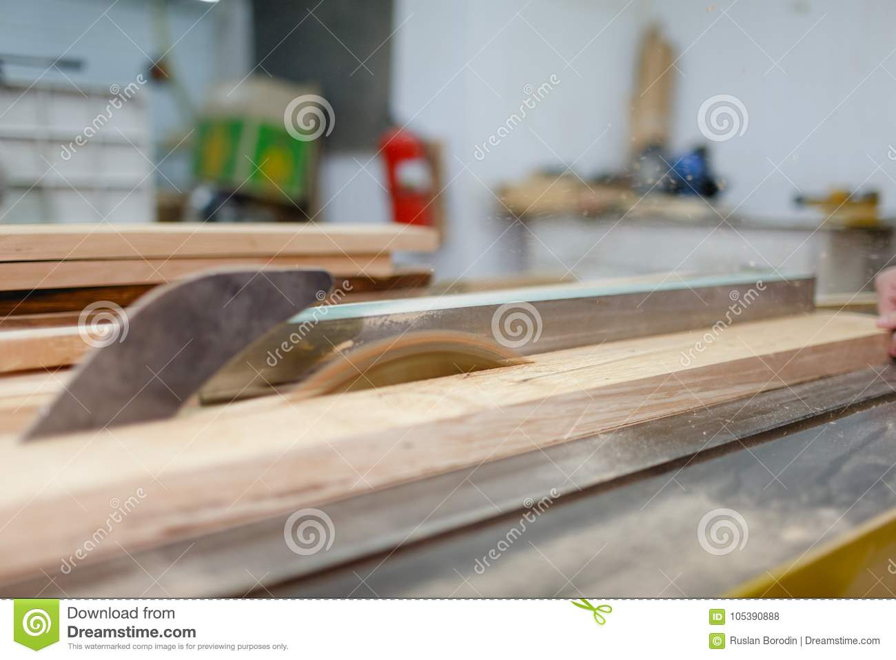 The machine saws the board on the machine and sawdust flying. View at an angle