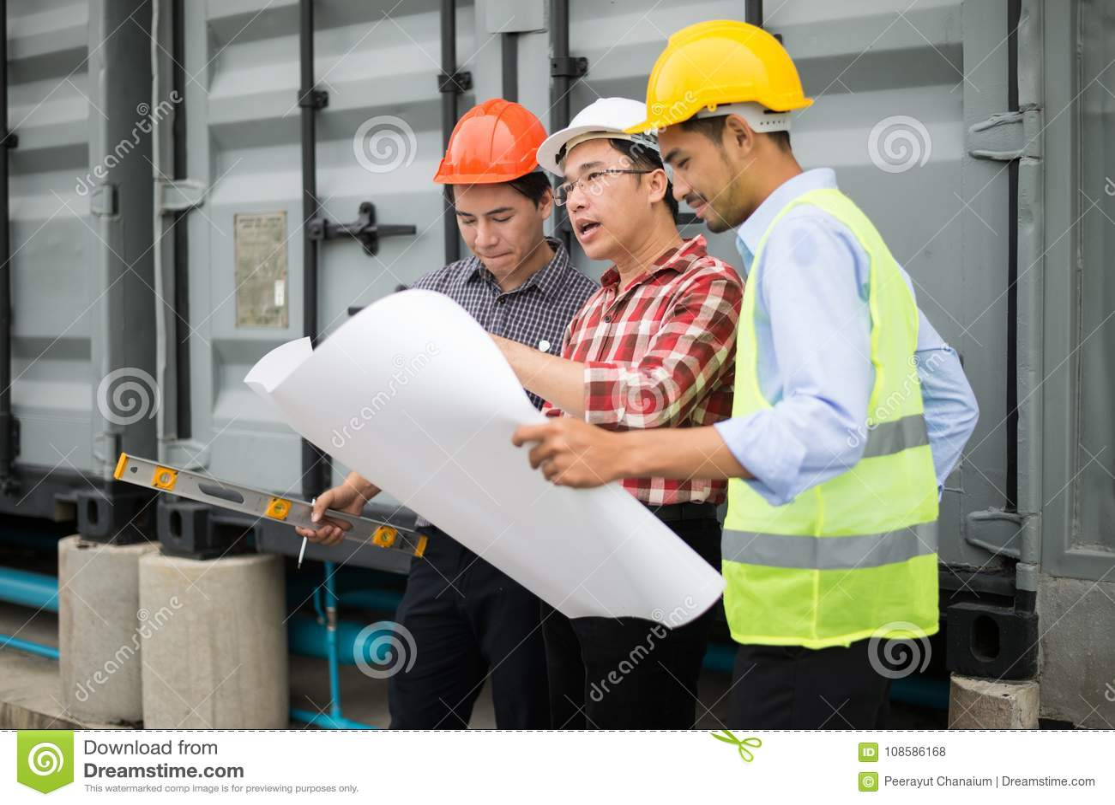 Machinez le casque de sécurité d équipe et le modèle de port en main ils travaillent à vérifier le progrès du chantier de constru