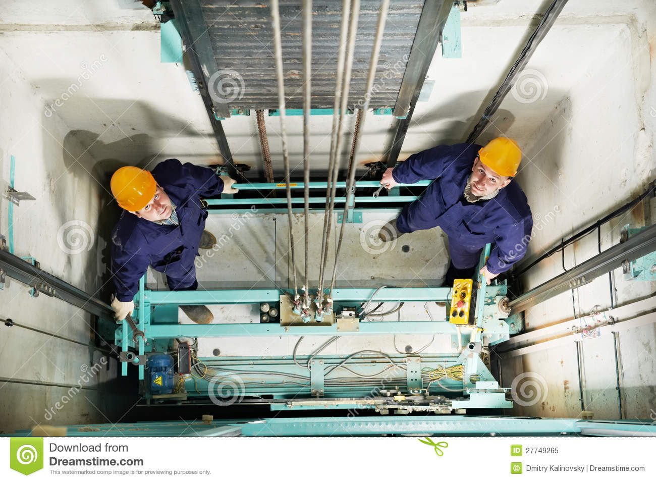 machinists adjusting lift in elevator hoist way stock