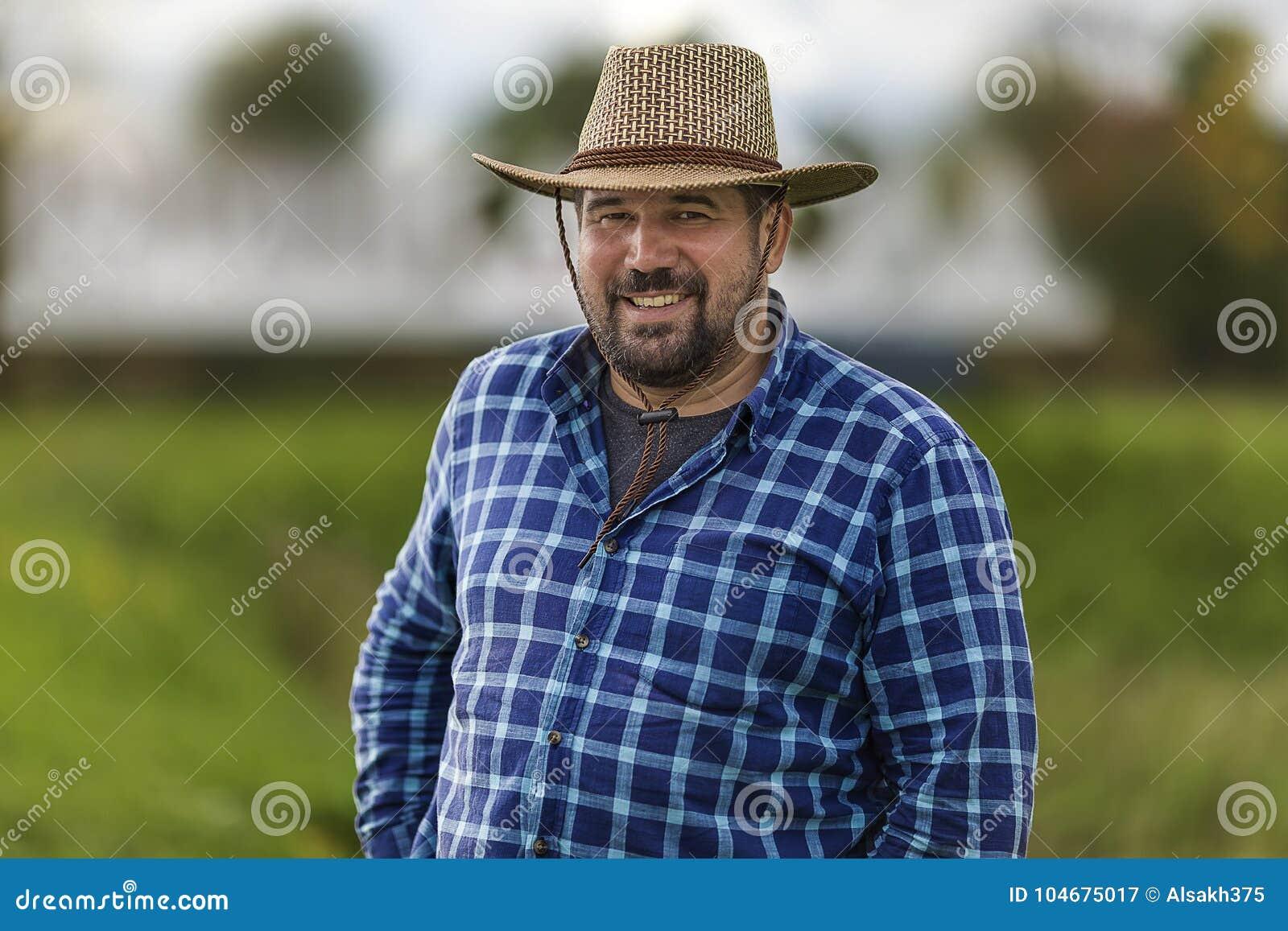 Machista brutal en el ulybayutsya del sombrero de vaquero y la vida feliz, llenos barbudos de positividad y de optimismo